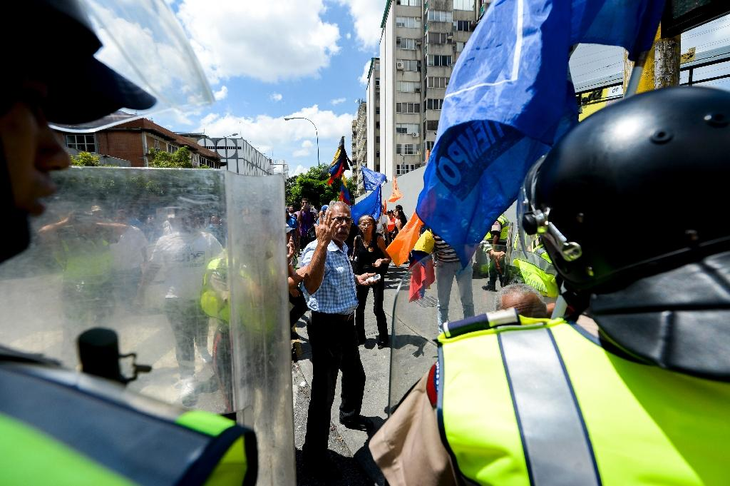 Venezuelan opposition activists are blocked by police during a march in Caracas demanding the government set a date for a recall referendum (AFP Photo/Federico Parra)