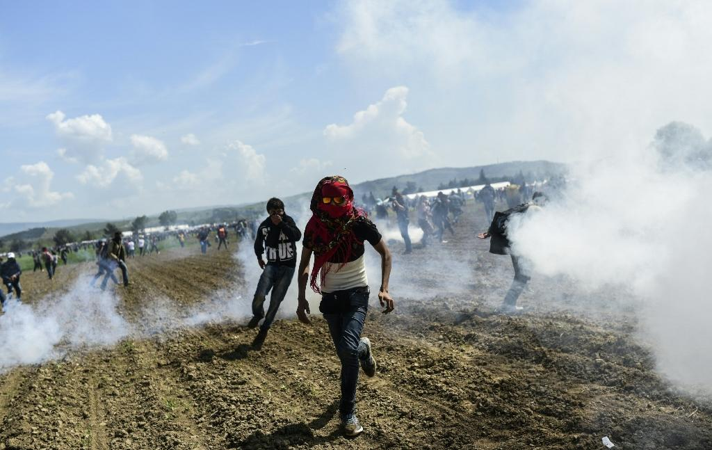 Refugees and migrants flee the tear gas as they clash with Macedonian police during a protest to reopen the border near their makeshift camp in the northern Greek border village of Idomeni, on April 10, 2016