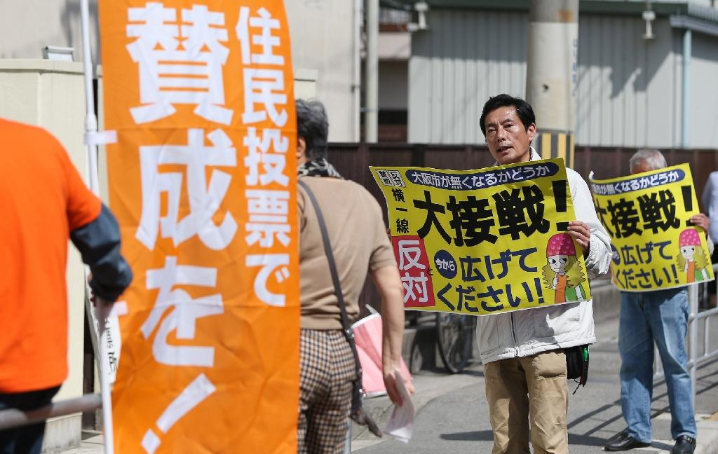 Canvassers urge people to vote outside a polling station in the city of Osaka, western Japan, on May 17, 2015