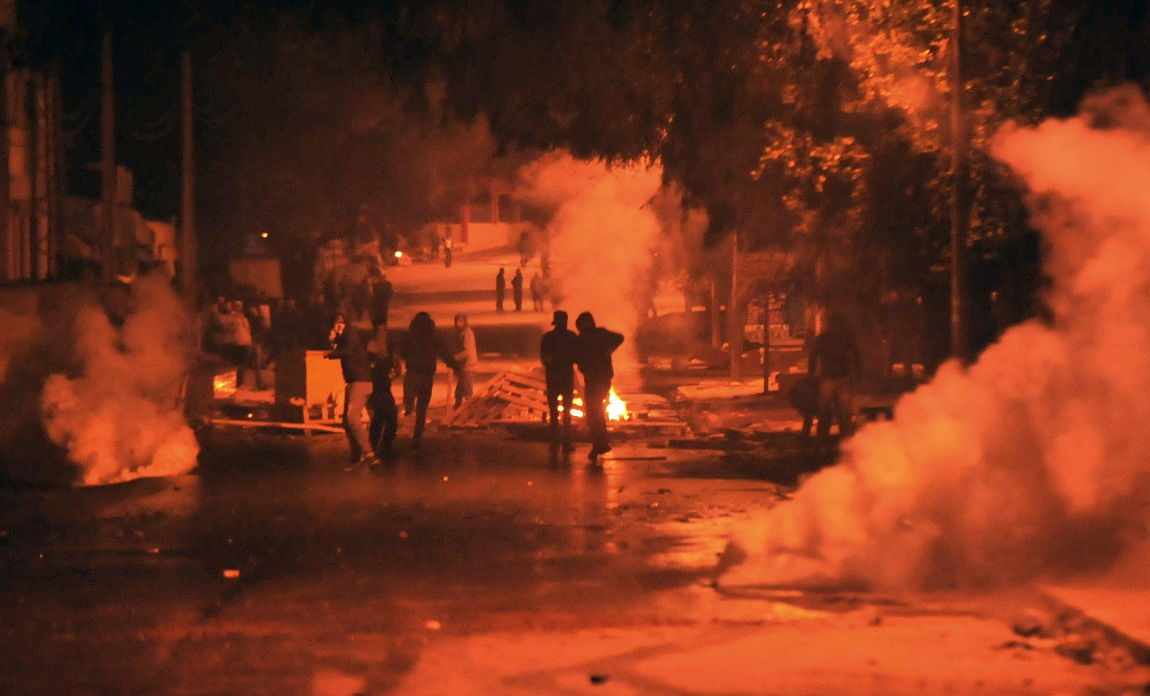 <p>Tear gas smoke billows as Tunisian protestors throw stones towards security forces in Tunis' Djebel Lahmer district early on Jan. 10, 2018 after price hikes ignited protests in the North African country. (Photo: Sofiene Hamdaoui/AFP/Getty Images) </p>