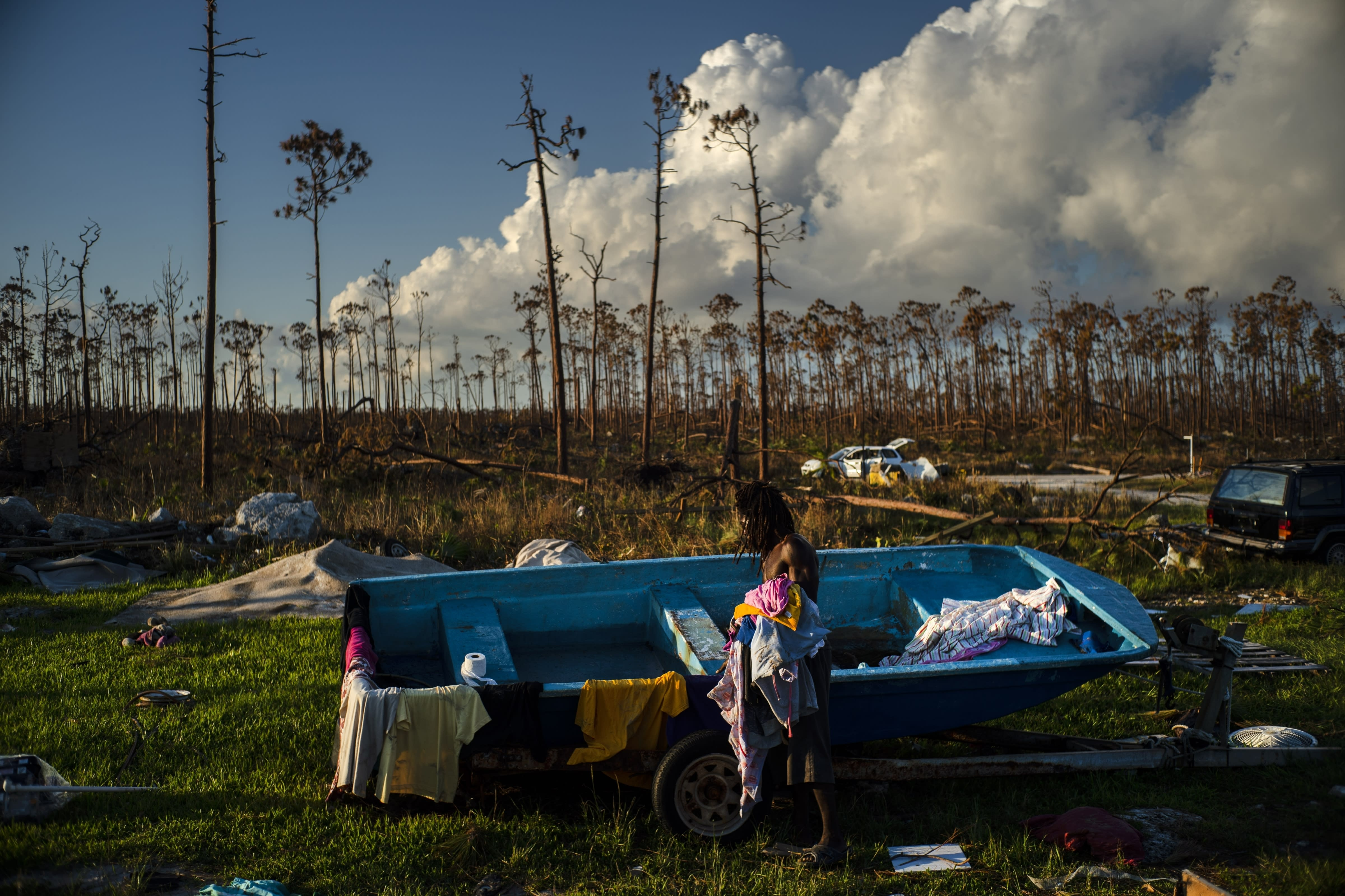 Valentino Ingraham washes clothing to remove salt and dirt amid the rubble of his mother's property destroyed by Hurricane Dorian in Rocky Creek East End, Grand Bahama, Bahamas, Sunday, Sept. 8, 2019. The motors of his family's boats were also destroyed. (AP Photo/Ramon Espinosa)