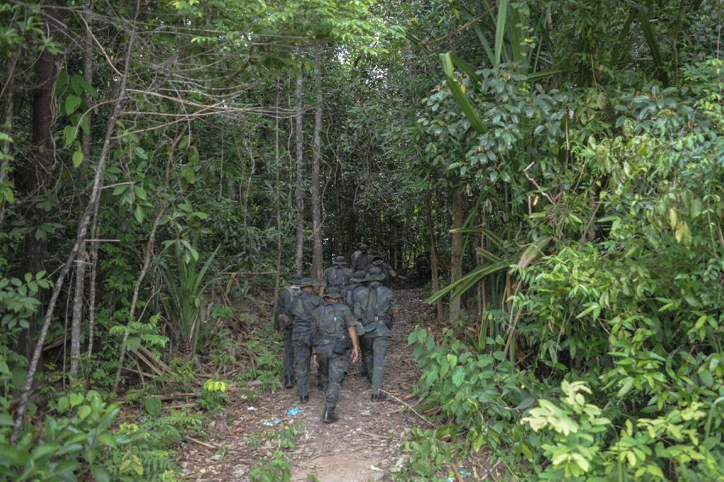 Royal Malaysian Police personnel walk towards the dense jungle area in Wang Kelian that leads to an abandoned migrant camp used by people-smugglers, on May 28, 2015 (AFP Photo/Mohd Rasfan)