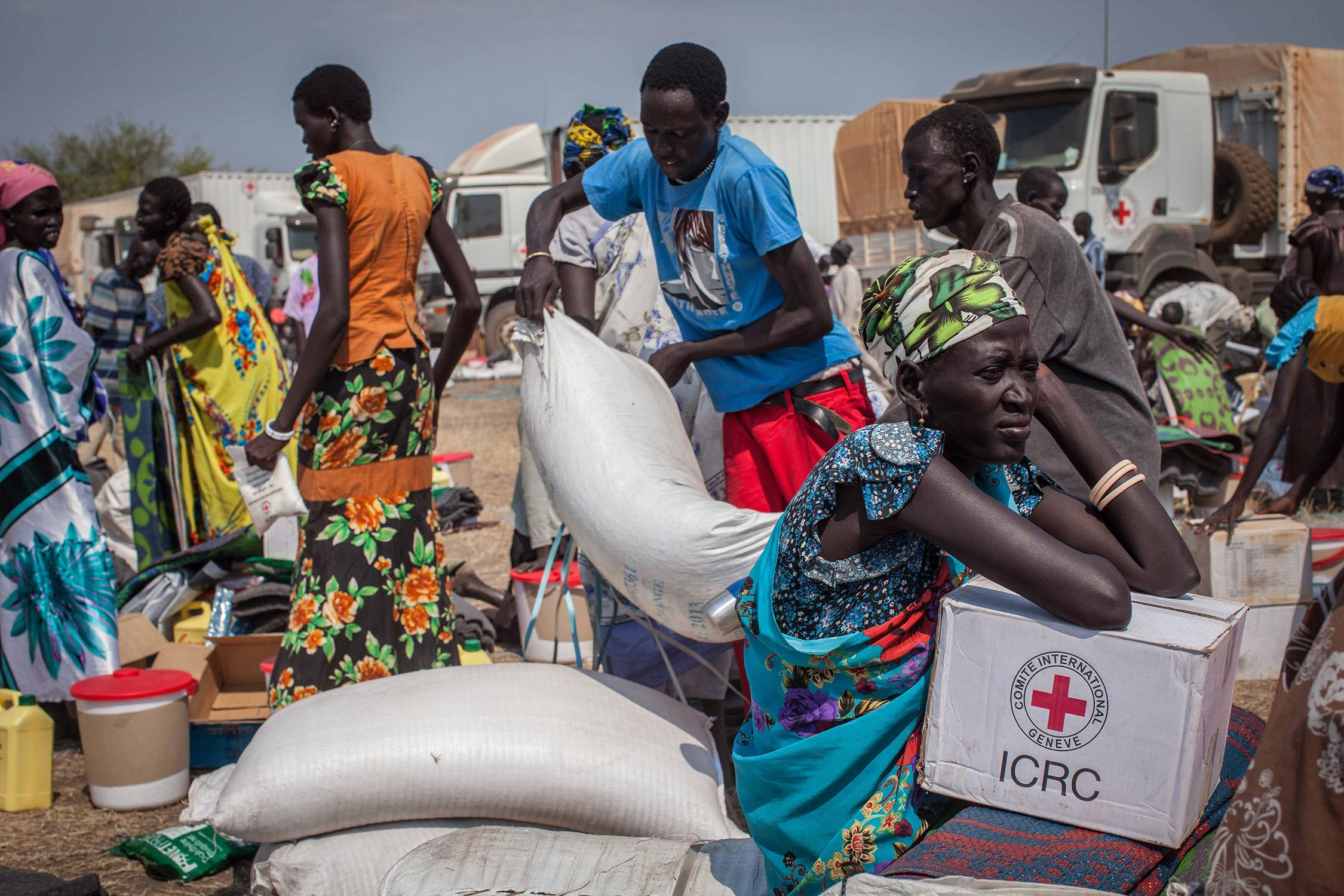 People receive food aid and other vital supplies on January 8, 2014 from the International Committee of the Red Cross, in Minkaman, South Sudan (AFP Photo/Nichole Sobecki)
