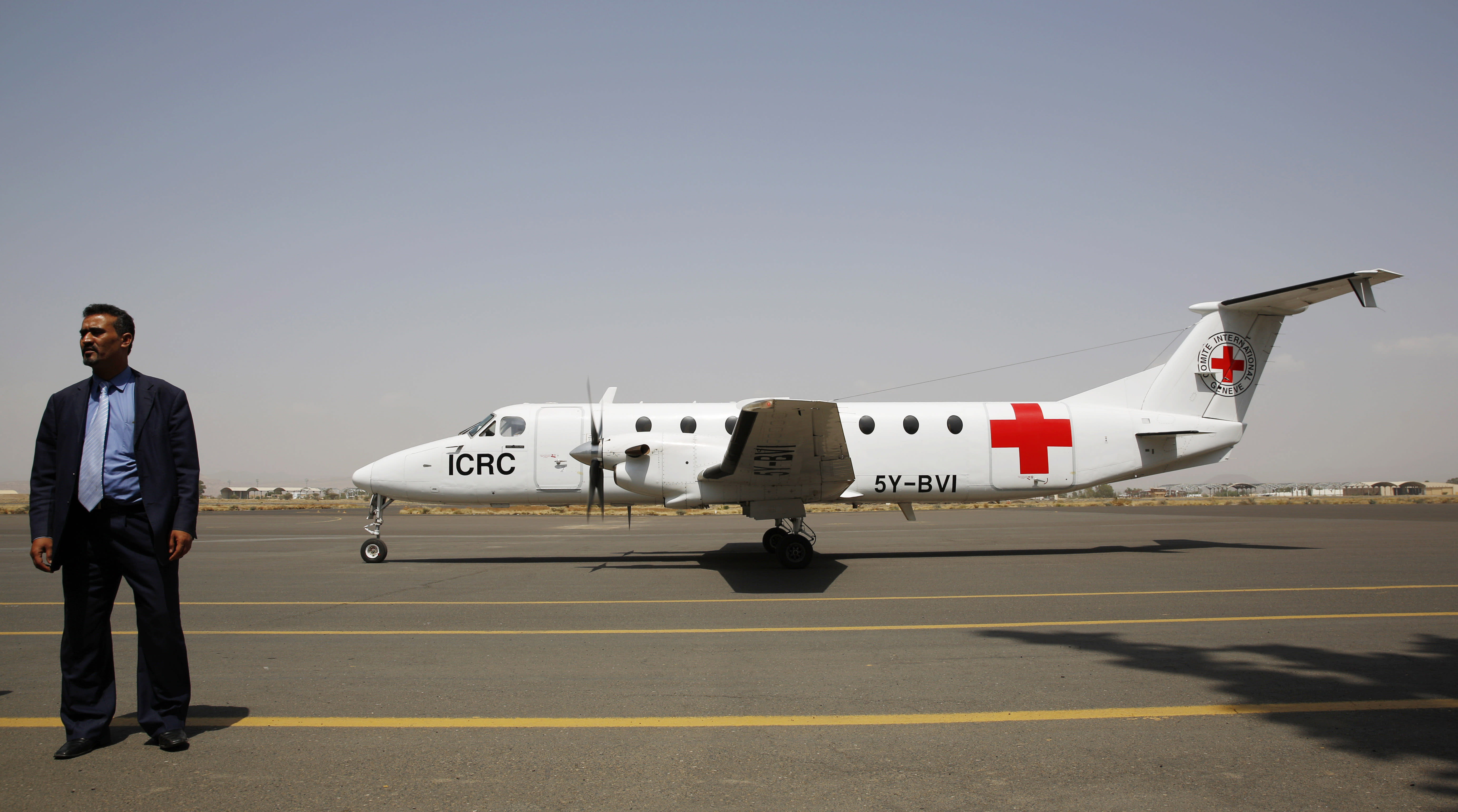 """FILE - In this Aug. 8, 2015 file photo, a Yemeni airport security official stands by a plane of the International Committee of the Red Cross on the tarmac of the international airport in Sanaa, Yemen. The Norwegian Refugee Council and CARE have slammed the Saudi-led coalition for its closure of the airport in Yemen's capital, saying this has prevented thousands of sick civilians from traveling abroad for urgent medical treatment, saying the Sanaa airport's three-year closure has amounted to a """"death sentence"""" for many sick Yemenis. The two aid groups appealed late Monday, Aug 5, 2019 on Yemen's warring parties to come to an agreement to reopen the airport for commercial flights to """"alleviate humanitarian suffering caused by the closure."""" (AP Photo/Hani Mohammed, File)"""
