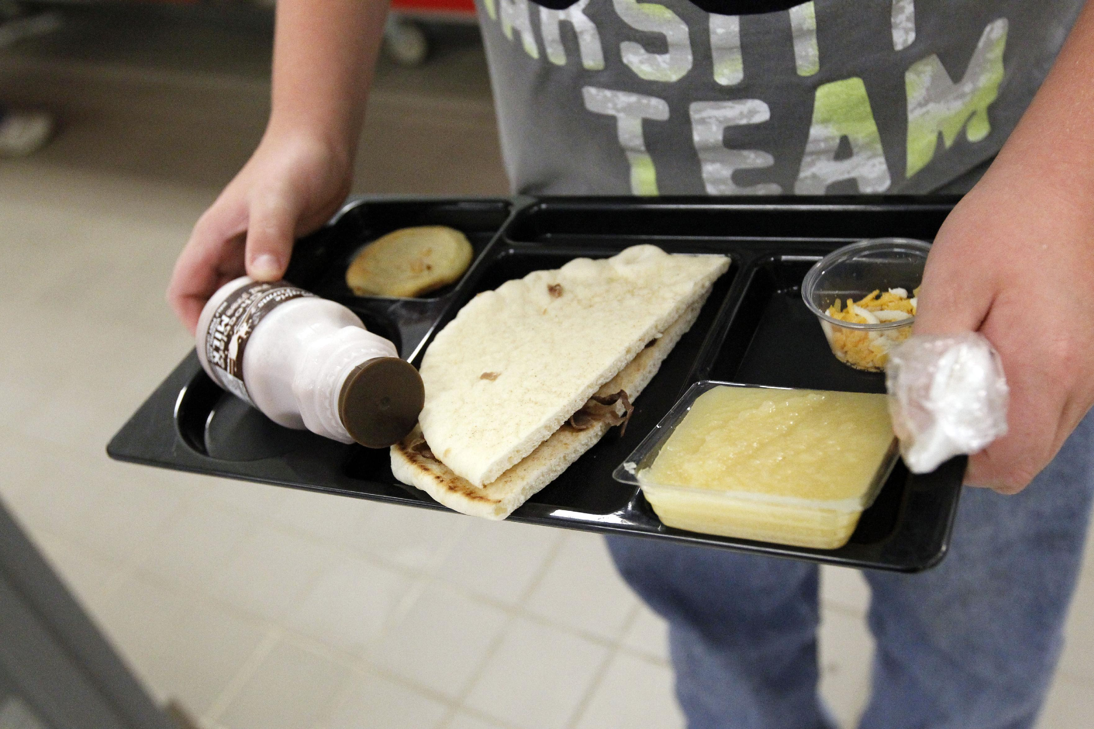 FILE - In this Wednesday, Sept. 12, 2012 file photo, a student at Eastside Elementary School in Clinton, Miss., holds a school lunch served under federal standards, consisting of a flatbread roast beef sandwich, apple sauce, chocolate milk and a cookie. After just one year, some schools across the nation are dropping out of what was touted as a healthier federal lunch program, complaining that so many students refused the meals packed with whole grains, fruits and vegetables that their cafeterias were losing money. (AP Photo/Rogelio V. Solis, File)