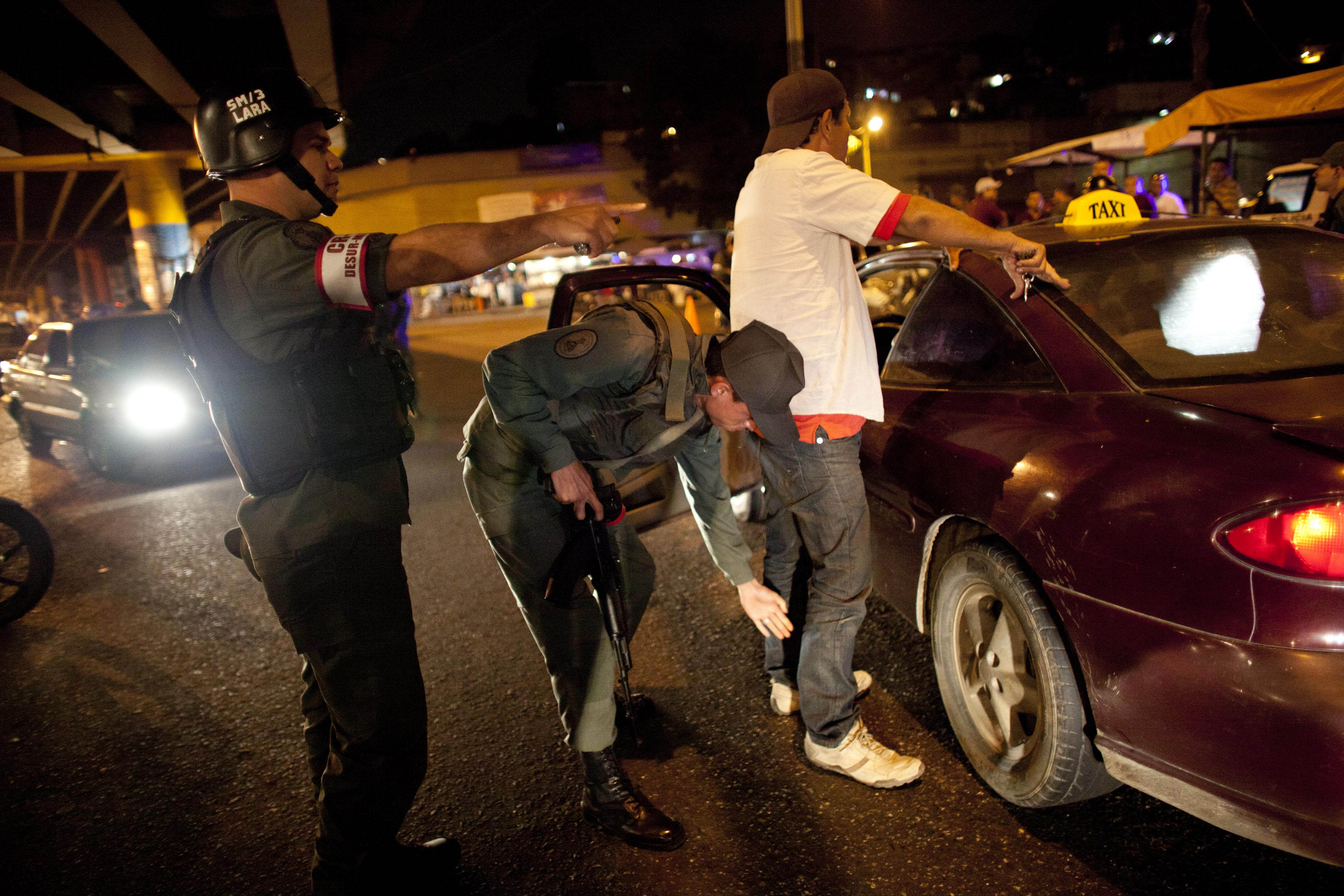 "In this May 14, 2013 photo, a National Guard soldier frisks a man outside his car at a checkpoint that is part of the ""Secure Homeland"" initiative in Petare, one of the most dangerous neighborhoods of Caracas, Venezuela. Since Monday, this scene is playing out day and night at dozens of military checkpoints set up here in the socialist government's latest attempt to control the oil-rich country's pandemic of violence. (AP Photo/Ariana Cubillos)"