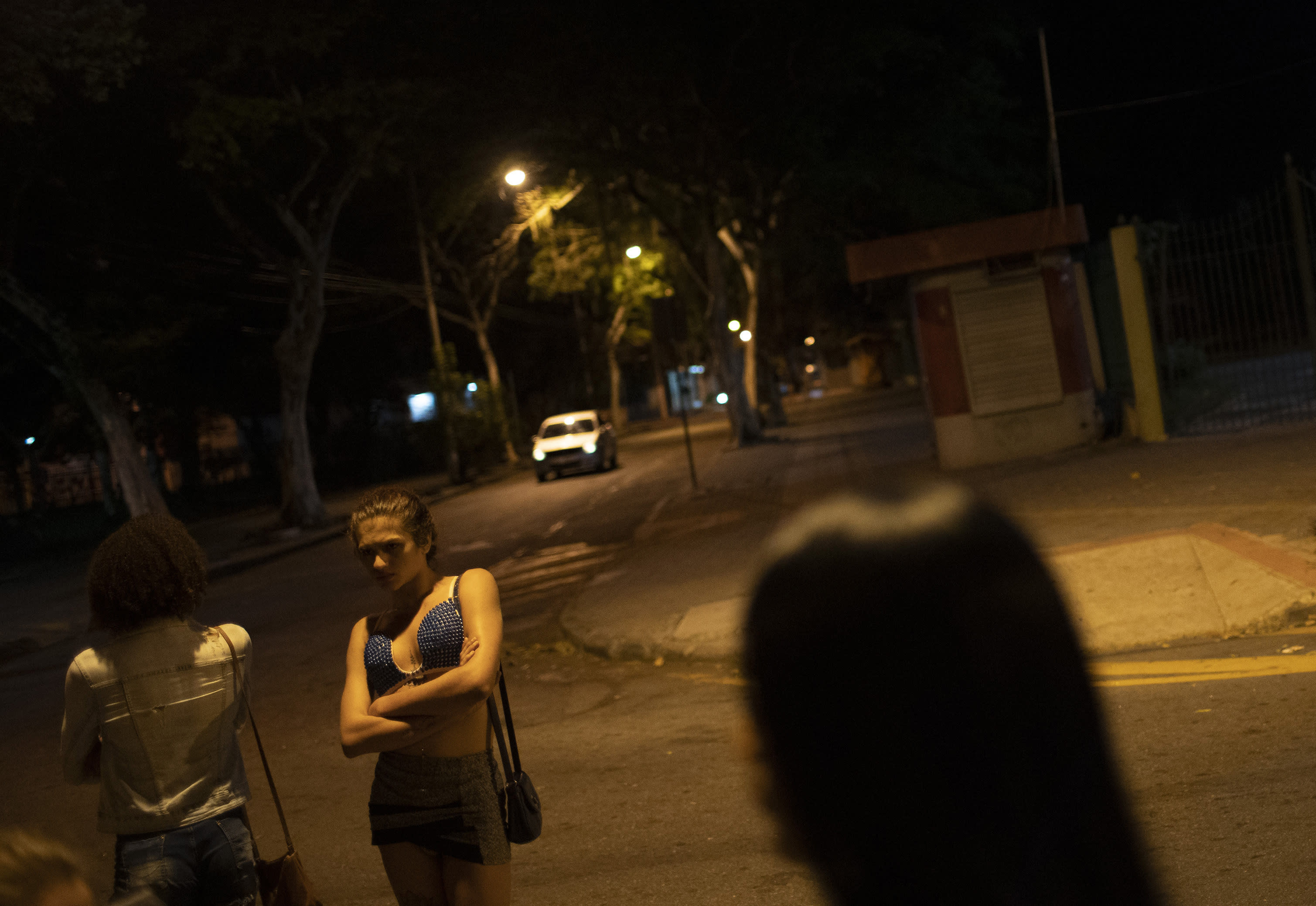 Transgender sex workers wait for customers in Niteroi, Brazil, Saturday, June 27, 2020, amid the new coronavirus pandemic. While some sex workers found refuge, others are stuck on the streets, hustling to earn enough to get by as the economy tanks. (AP Photo/Silvia Izquierdo)