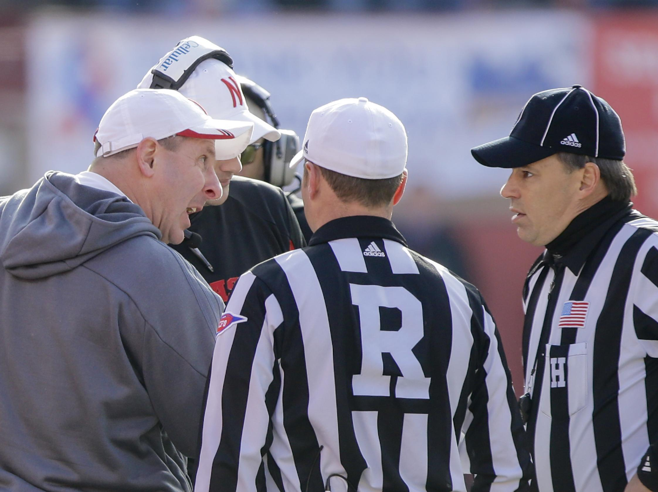 Nebraska head coach Bo Pelini, left, protests a pass interference call to referee Alex Kemp, center, and linesman Steven Matarante, right, in the third quarter of an NCAA college football game against Iowa in Lincoln, Neb., Friday, Nov. 29, 2013. Iowa won 38-17. (AP Photo/Nati Harnik)