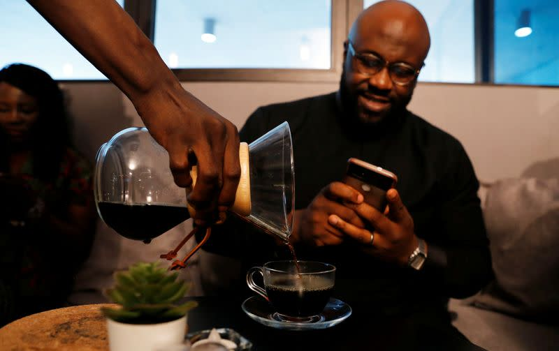 A customer takes a picture as his coffee is served at Mai Shayi cafe in Victoria Island, Lagos