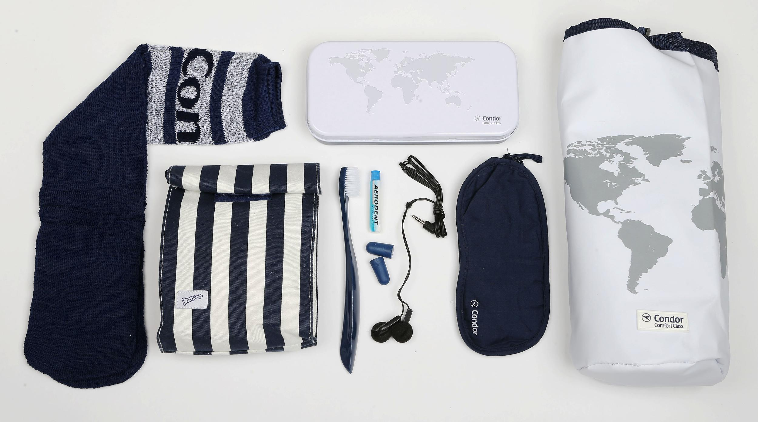 <p><strong>What do you get?</strong> Premium Economy: There is a nautical theme running through the Premium Economy kits which consist of a laundry bag and a cosmetic pouch in navy blue and white stripes.<br /> Comfort Class: The Comfort Class kits come in a wine cooling bag and a metal tin, both decorated with a world map motif.<br /> The contents of all the kits are the same but the Comfort Class customers do not get earphones inside their bags. They contain: Eye mask, socks, toothbrush, ear plugs, ear phones<br /> <strong>Best bit of the kit?</strong> The wine cooler.</p>