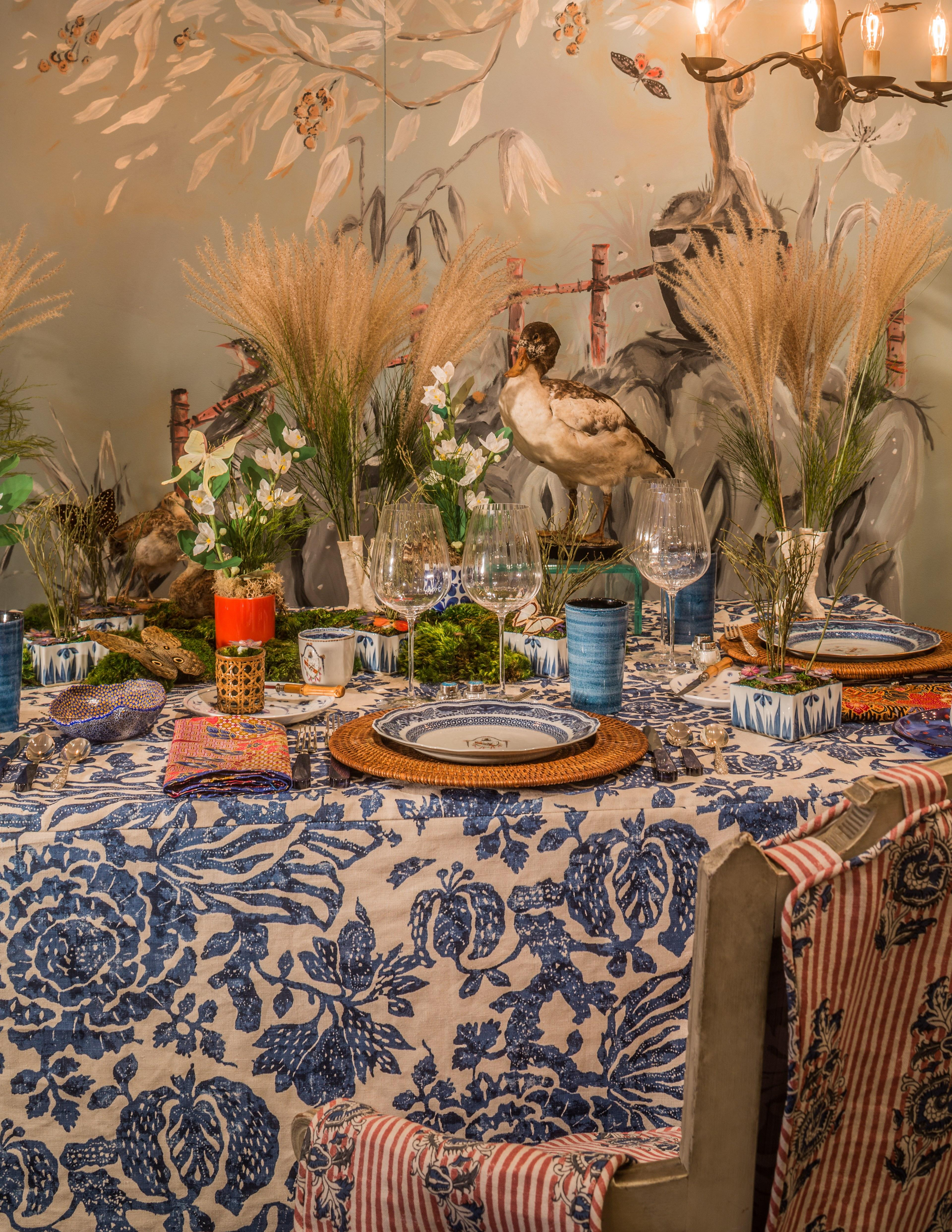 """Madame de Rothschild made a second appearance at the table of designer and author P. Gaye Tapp. Dubbed """"Le Style Pauline,"""" Tapp's tablescape juxtaposes Post's Chinese export porcelain with modern flatware and glasses. North Carolina–based Tapp is well positioned to speculate on the entertaining style of such stylish women; she's the author of <em>How They Decorated: Inspiration from Great Women of the Twentieth Century</em> (<a href=""""https://www.amazon.com/How-They-Decorated-Inspiration-Twentieth/dp/0847847411/ref=sr_1_1/140-7613939-5834508?ie=UTF8&qid=1491754869&sr=8-1&keywords=how%20they%20decorated%20amazon"""" rel=""""nofollow noopener"""" target=""""_blank"""" data-ylk=""""slk:Rizzoli,"""" class=""""link rapid-noclick-resp"""">Rizzoli,</a> $55). """"It's only natural that I turn to her legendary Grand Mouton tablescapes for The Artistic Table inspiration,"""" Tapp explains. """"Pauline de Rothschild needed look no further than the exquisitely framed eighteenth-century Chinese painted panels in her Mouton bedroom. Those panels might come to life on her table landscapes — petite orchards of wild cherry, or a small forest of branches in cache-pot. My table also takes its cues from those panels and the taxidermy birds de Rothschild had in her bedroom."""" Tapp enlisted decorative painter Jimmie Henslee to interpret de Rothschild's panels as a mural behind her table."""