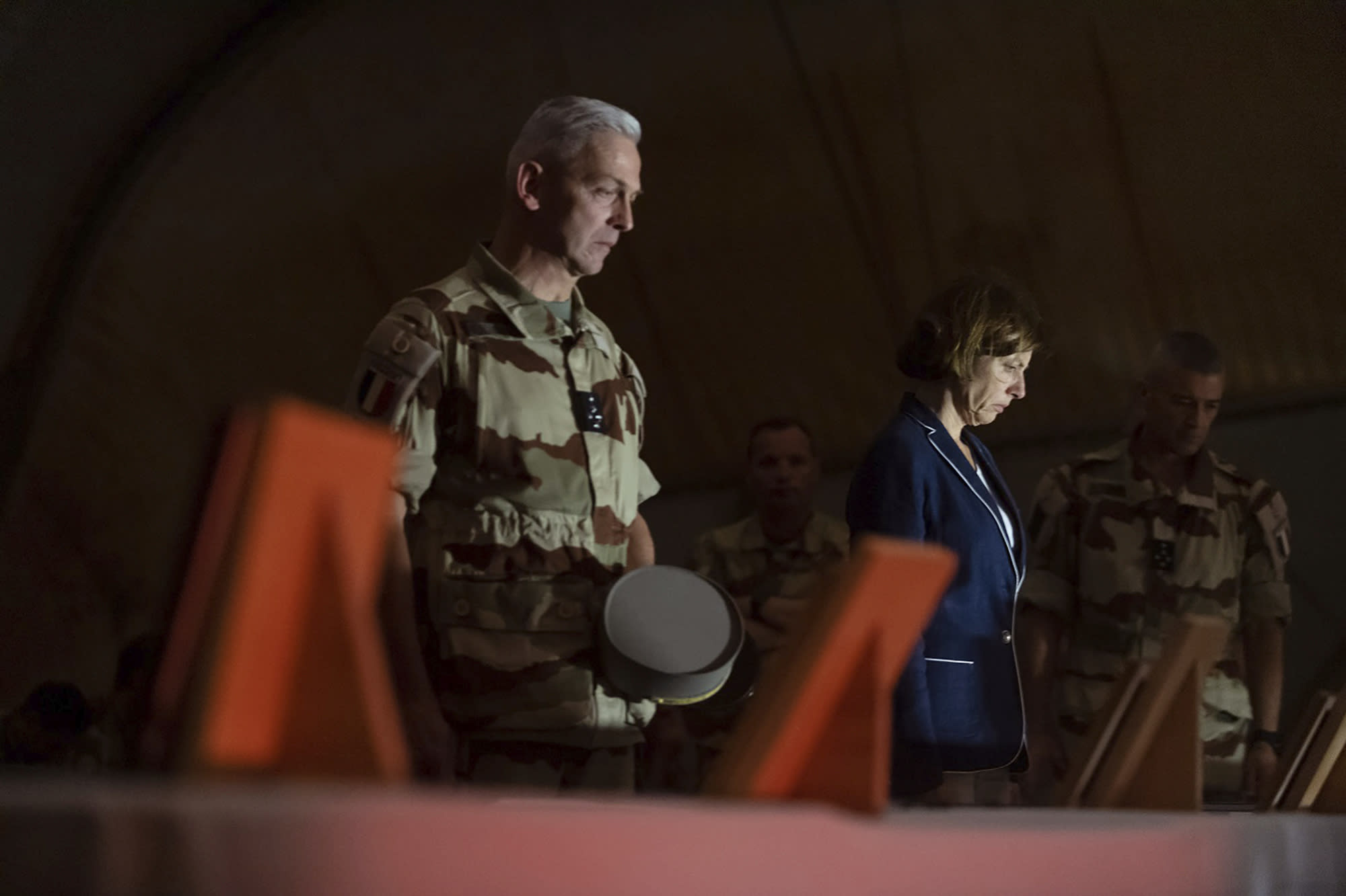 In this Wednesday, Nov. 27, 2019, photo provided by French Defense Communication and Audiovisual Department (ECPAD), French Defense Minister Florence Parly, right, and French Army Chief of Staff Gen. Francois Lecointre, pay their respects to the 13 French soldiers, in Gao, Mali. Parly arrived in northern Mali on Wednesday after a helicopter collision killed 13 French soldiers fighting Islamic State group-linked extremists, while some in the West African country debated France's military presence. (Thomas Peudeleux/ECPAD via AP)