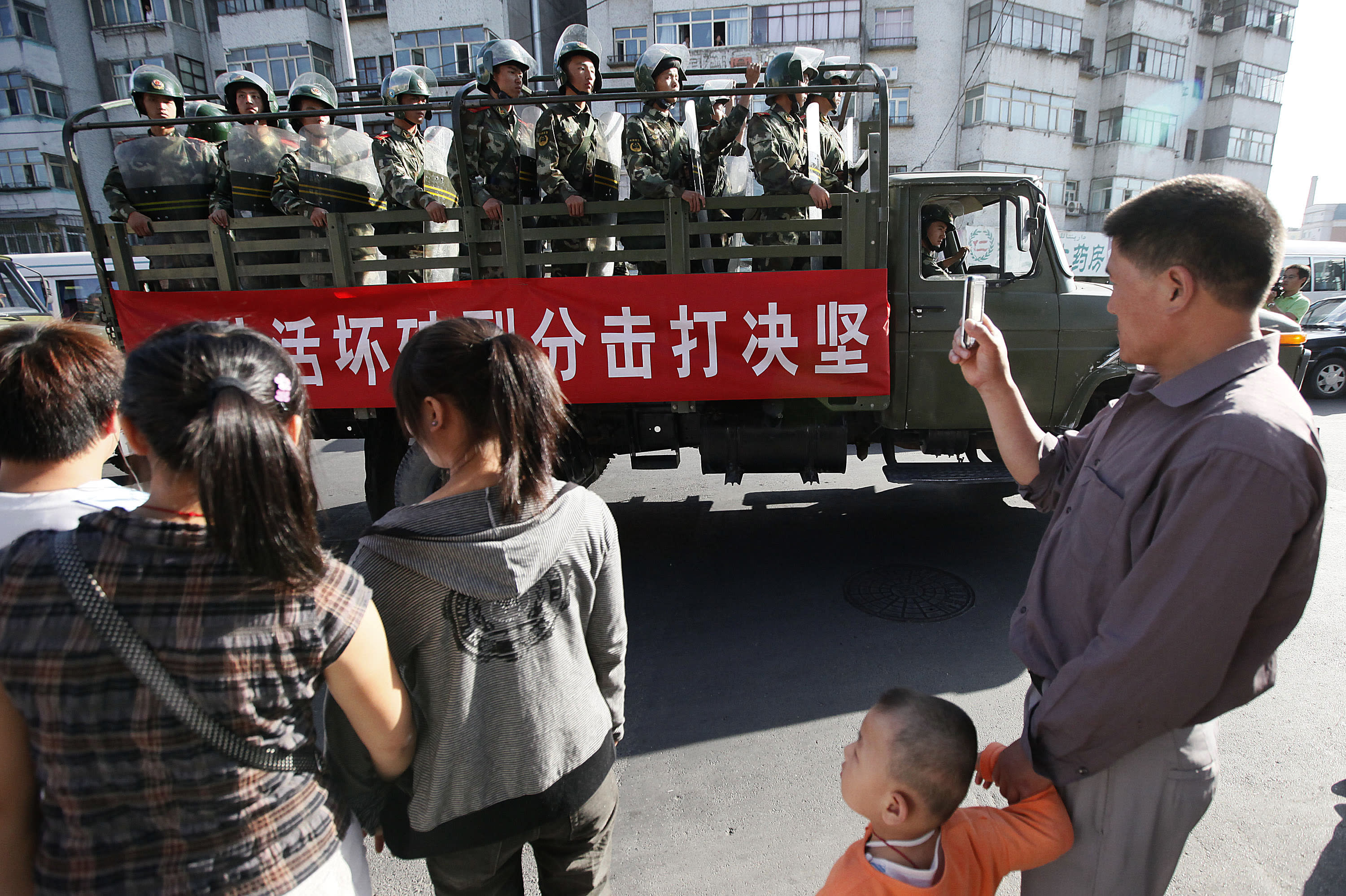 """FILE - In this file photo taken Thursday, July 9, 2009, bystanders look at a truckload of paramilitary police with a banner which reads """"Determined crackdown on separatist activities"""" patrol in the aftermath of riots in Urumqi in western China's Xinjiang province, Analysts say the Urumqi riots in 2009 set in motion the harsh security measures now in place across Xinjiang, where about 1 million Uighurs, Kazakhs and other Muslims are estimated to be held in heavily-guarded internment camps _ also called """"re-education"""" camps _ which the Chinese government describes as vocational training centers. (AP Photo/Eugene Hoshiko, File)"""