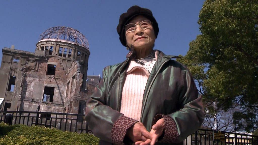 Hiroshima survivor Hashizume Bun stands next to the Hiroshima Peace Memorial in 2011
