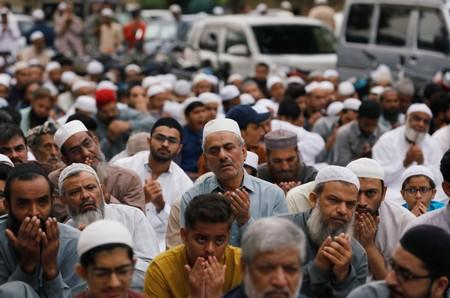 Men attend Eid al-Adha prayers outside a mosque along a street in Karachi,