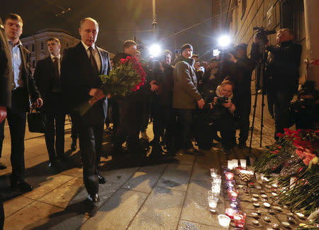 Russian president Vladimir Putin puts flowers down outside Tekhnologicheskiy Institut metro station in St. Petersburg