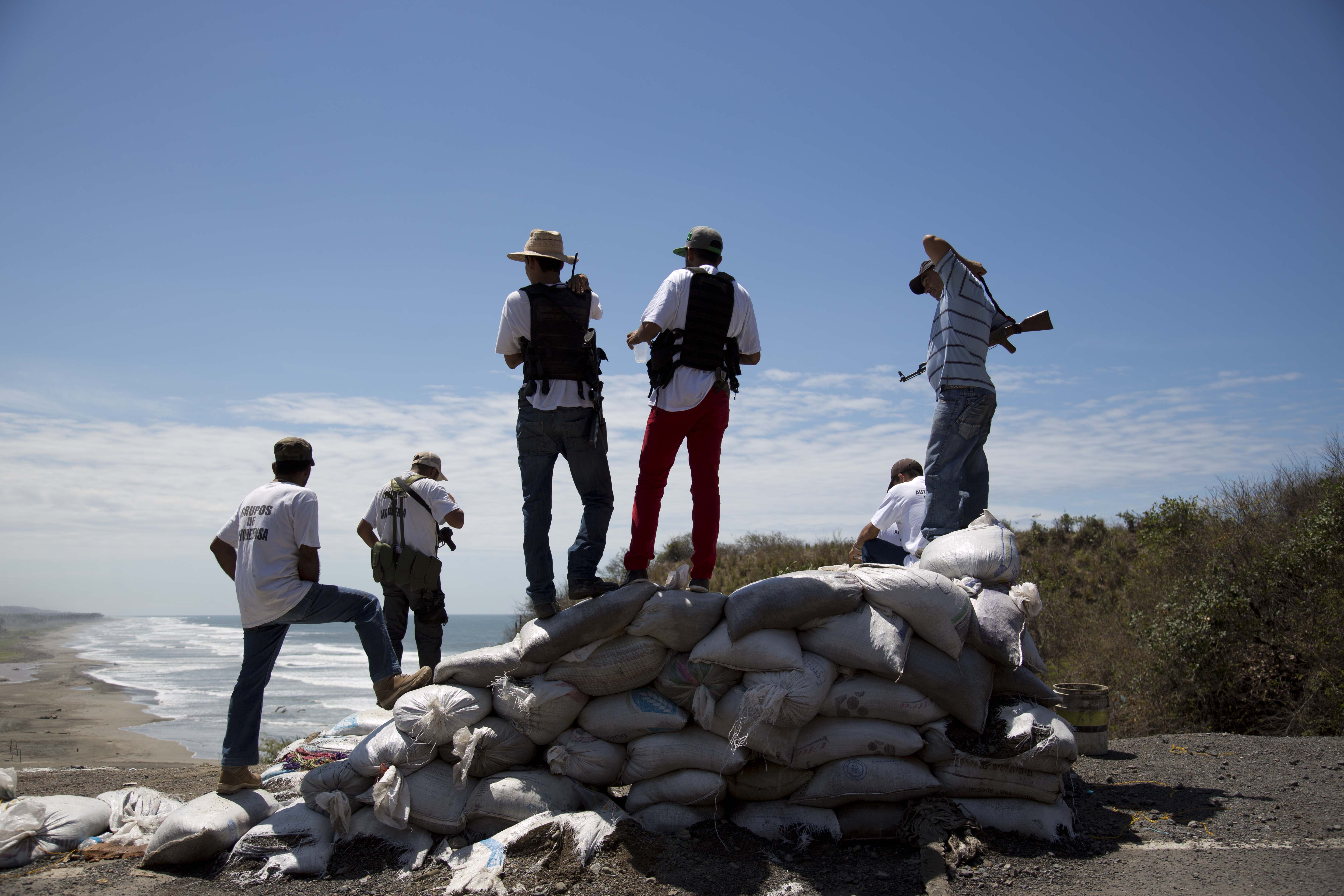 Armed men belonging to the Self-Defense Council of Michoacan (CAM) look out toward the sea as they guard a checkpoint set up by the self-defense group in Chuquiapan on the outskirts of the seaport of Lazaro Cardenas in western Mexico, Friday, May 9, 2014. Mexico's government plans on Saturday to begin demobilizing the vigilante movement that largely expelled the Knights Templar cartel when state and local authorities couldn't. But tension remained on Friday in the coastal part of the state outside the port of Lazaro Cardenas, where some self-defense groups plan to continue as they are, defending their territory without registering their arms. (AP Photo/Eduardo Verdugo)
