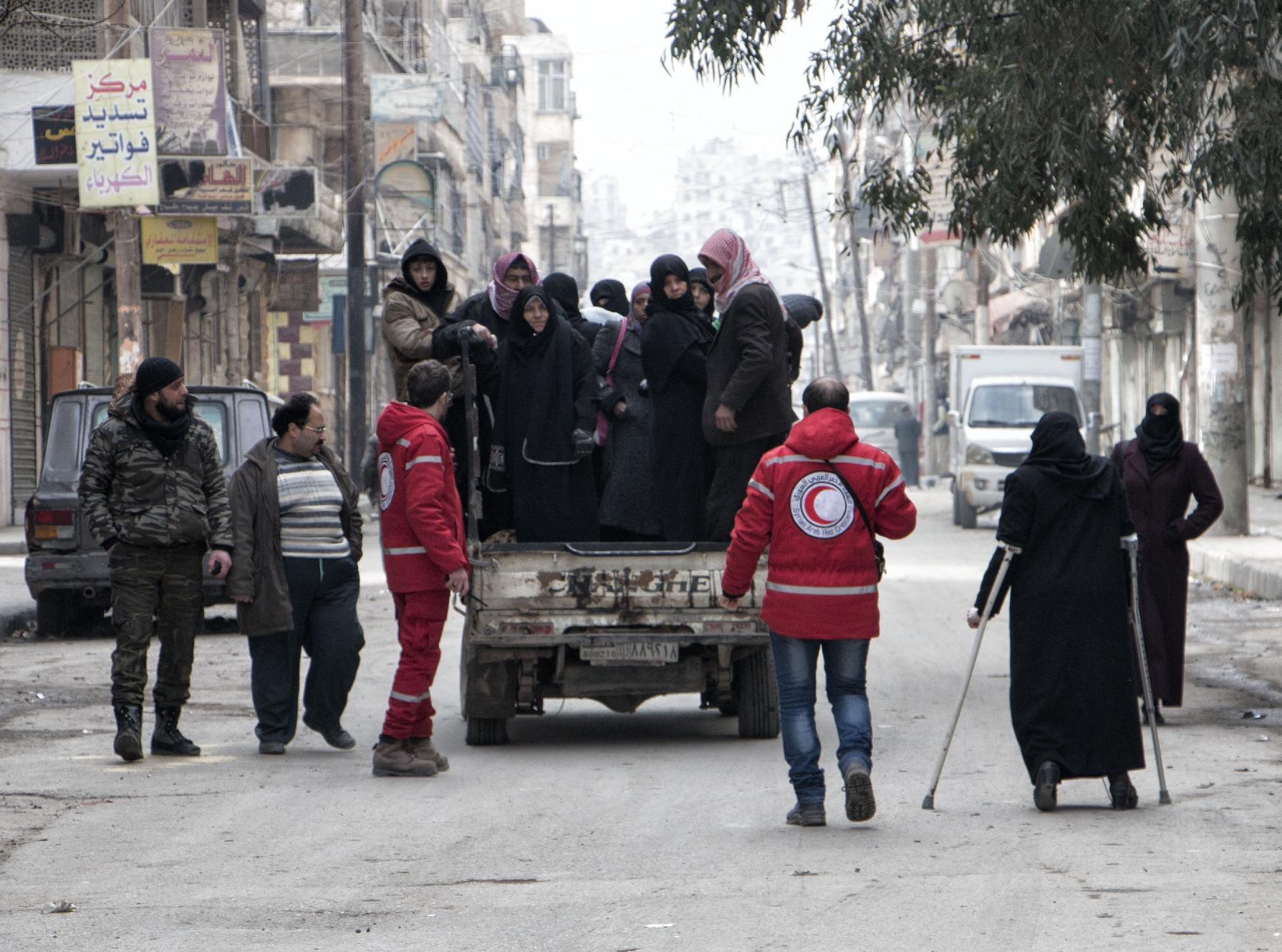 Members of the Syrian Red Crescent transport Syrians from a rebel-controlled area of Aleppo to the regime held area of the city on January 28, 2015 (AFP Photo/Karam Al-Masri)