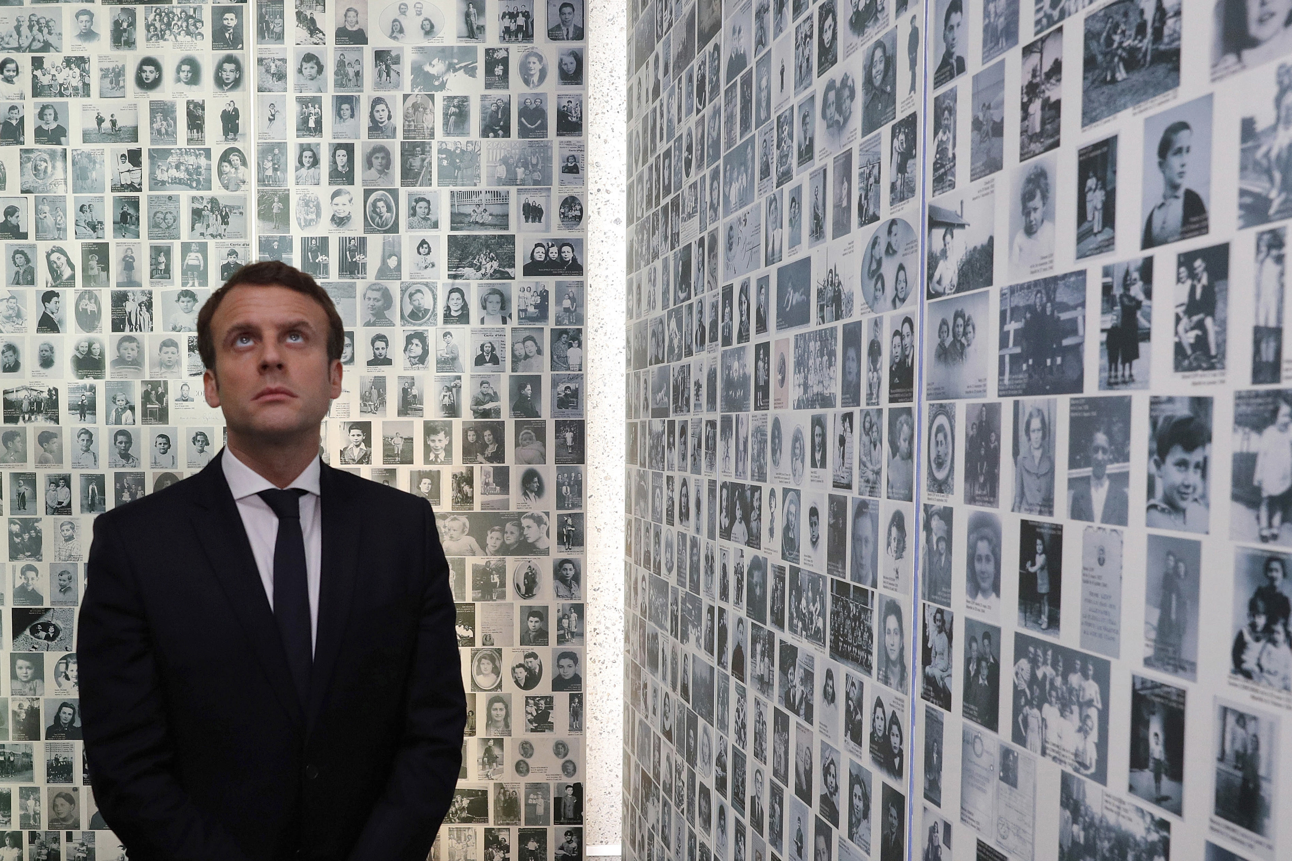 FILE - In this Sunday, April 30, 2017 file picture, independent centrist presidential candidate Emmanuel Macron looks at some of the 2,500 photographs of young Jews deported from France, during a visit to the Shoah memorial in Paris, France. France's prime minister is sounding the alarm over a sharp rise in anti-Semitic acts this year, pledging to increase efforts to punish perpetrators and police hate speech online.(Philippe Wojazer/Pool Photo via AP, File)