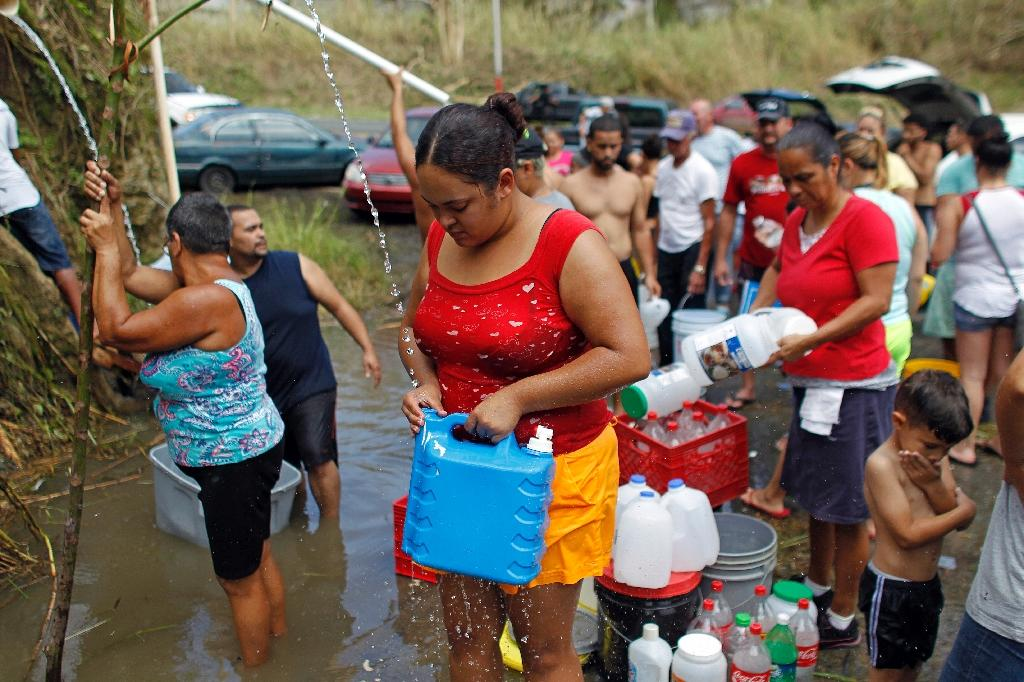 People collect water from a natural spring created by the landslides in Corozal, west of San Juan, Puerto Rico, on September 24, 2017 after Hurricane Maria struck (AFP Photo/Ricardo ARDUENGO)