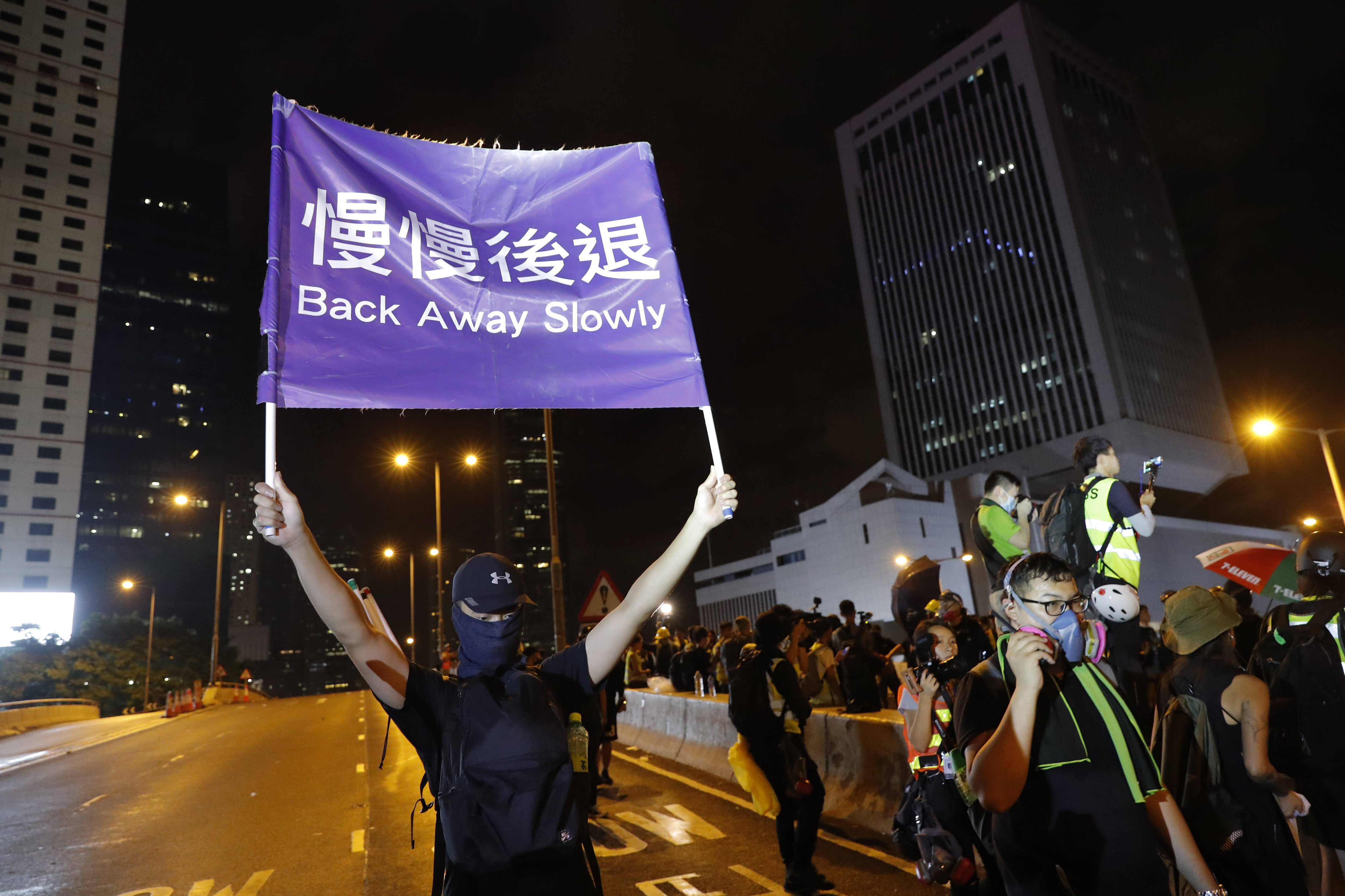 """A demonstrator holds up a sign reading """"Back away slowly"""" to encourage other demonstrators to leave, near the Chinese Liaison Office in Hong Kong, Sunday, Aug. 18, 2019. Protesters turned Hong Kong streets into rivers of umbrellas Sunday as they marched through heavy rain from a packed park and filled a major road in the Chinese territory, where mass pro-democracy demonstrations have become a regular weekend activity this summer. (AP Photo/Vincent Thian)"""
