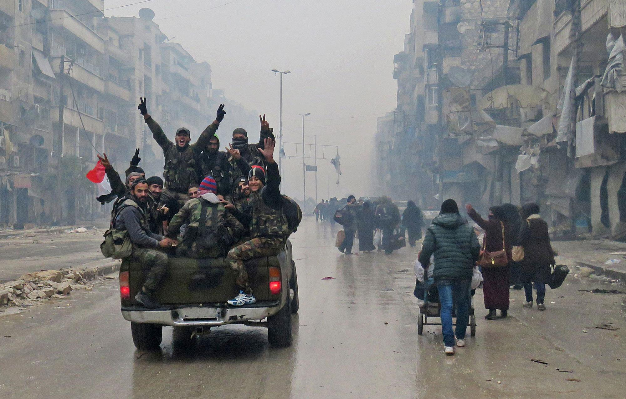<p>Syrian pro-regime fighters, gesture as they drive past residents fleeing violence in the restive Bustan al-Qasr neighbourhood, in Aleppo's Fardos neighbourhood on December 13, 2016, after regime troops retook the area from rebel fighters. Syrian rebels withdrew from six more neighbourhoods in their one-time bastion of east Aleppo in the face of advancing government troops, the Syrian Observatory for Human Rights said. (Stringer/AFP/Getty Images) </p>