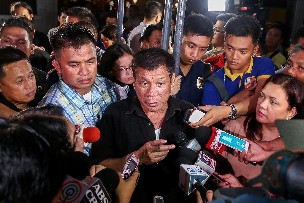 Philippines' president-elect Rodrigo Duterte (C) speaks to journalists in Davao City