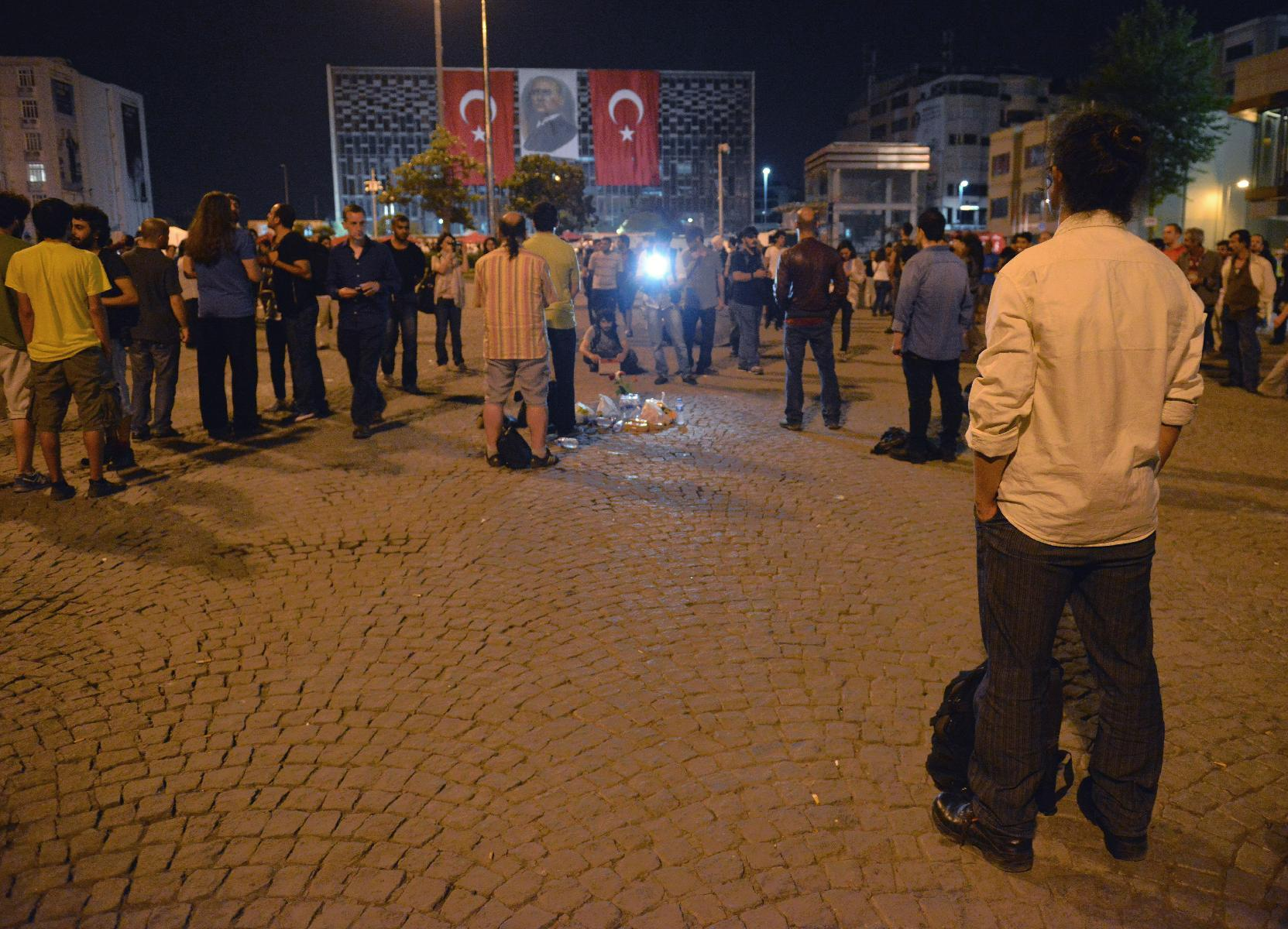 Erdem Gunduz, right, stands silently on Taksim Square in Istanbul, Turkey, early Tuesday, June 18, 2013. After weeks of confrontation with police, sometimes violent, Turkish protesters are using a new form of resistance: standing silently. The development started late Monday when a solitary man began standing in passive defiance against Prime Minister Recep Tayyip Erdogan's authority at Istanbul's central Taksim Square. The square has been sealed off from mass protests since police cleared it over the weekend. The man has identified himself as Erdem Gunduz, a performance artist. His act has sparked imitation by others in Istanbul and other cities. It has provoked widespread comment on social media. (AP Photo)
