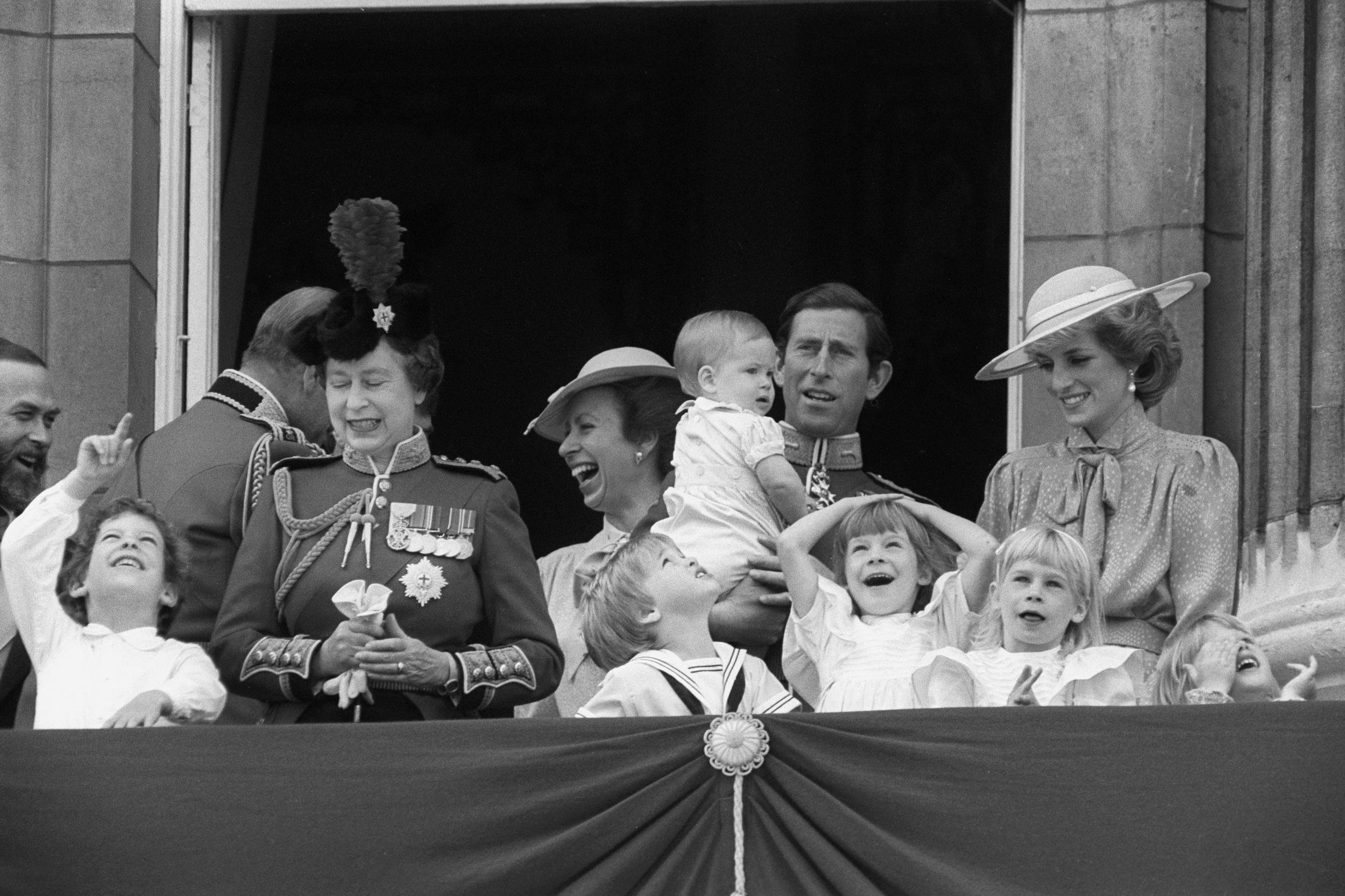 Members of the Royal family on the balcony of Buckingham Palace, London, to watch the fly-past after the Trooping the Colour ceremony. Baby Prince Harry wriggles in the arms of his father, the Prince of Wales, who is flanked by the Princess Anne (l) and the Princess of Wales. Children in the front row (l-r) are Prince William of Wales, Lady Davina Windsor, the eight-year-0old daughter of the Duke and Duchess of Gloucester.