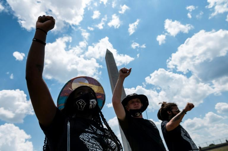 Protesters raise their fists during a rally against racism in front of the Washington Monument on July 4, 2020, a national holiday darkened by the coronavirus pandemic, continuing racial tensions and angry words from President Donald Trump (AFP Photo/ROBERTO SCHMIDT)