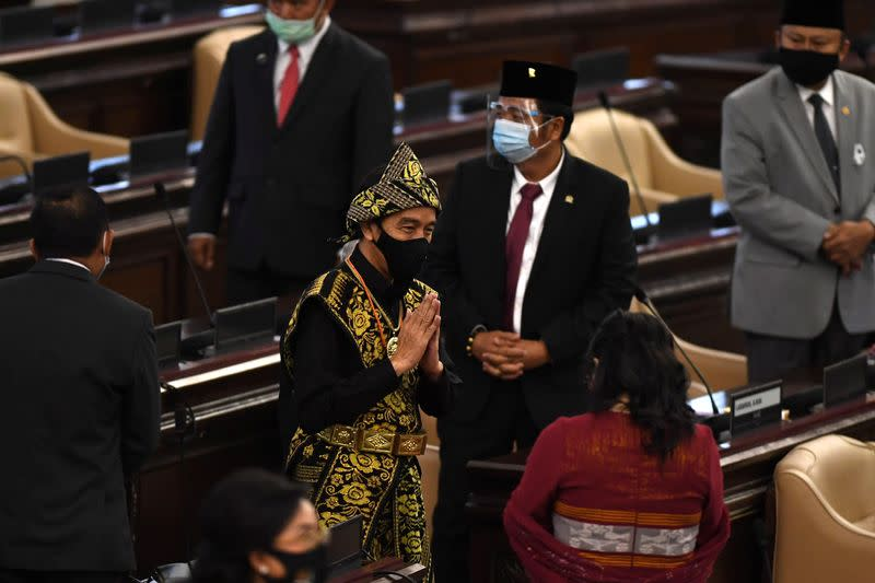 Indonesian President Joko Widodo wearing protective mask salutes to Indonesian parliament members as he arrives before delivering a speech ahead of the 75th Independence Day, at the parliament building in Jakarta