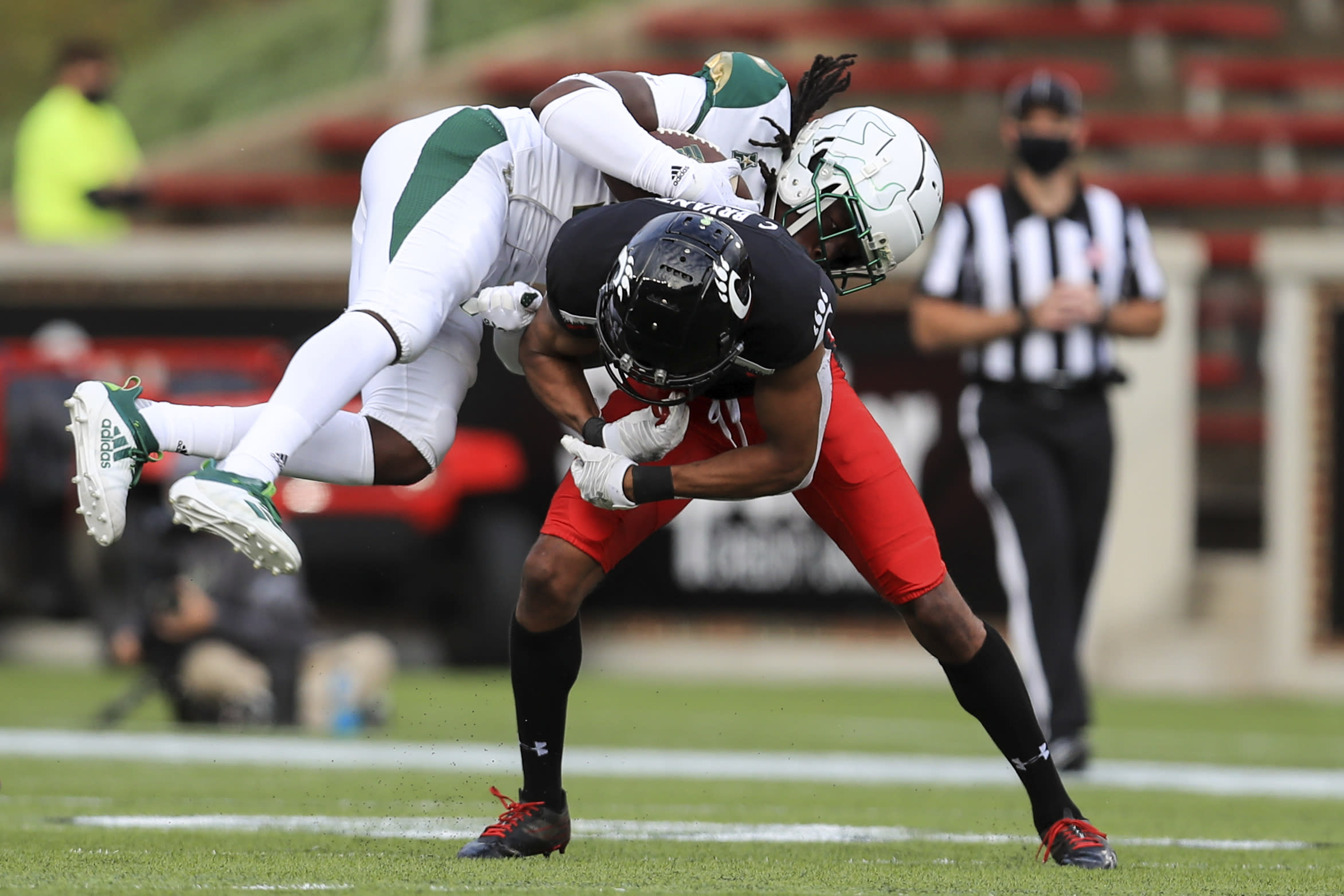 South Florida wide receiver Randall St. Felix, top, makes a catch and is upended by Cincinnati cornerback Coby Bryant, bottom, during the second half of an NCAA college football game, Saturday, Oct. 3, 2020, in Cincinnati. (AP Photo/Aaron Doster)