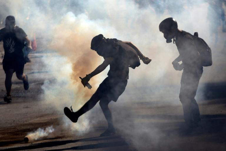Demonstrators clash with riot police during a protest against the government in Santiago on November 26, 2019