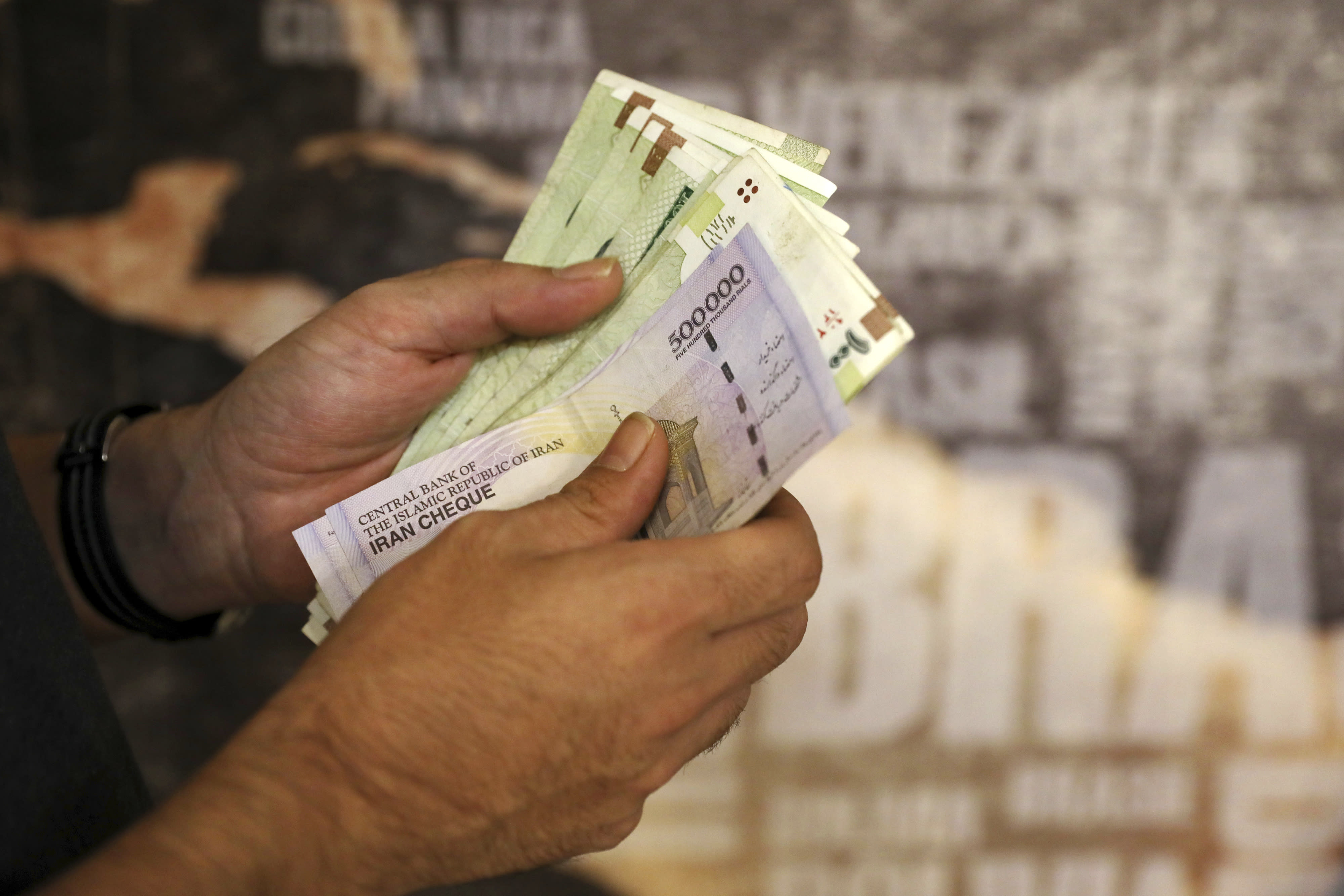 FILE - In this Aug. 21, 2019 file photo, a man counts his banknotes and traveler checks in Tehran, Iran. On Sunday, Sept 20, 2020, Iran dismissed U.S. efforts to restore all U.N. sanctions on the country as mounting economic pressure from Washington pushed the local currency down to its lowest level ever. (AP Photo/Ebrahim Noroozi, File)