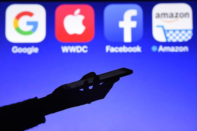 This photograph taken on September 28, 2017, shows a smartphone being operated in front of GAFA logos (acronym for Google, Apple, Facebook and Amazon web giants) as background in Hédé-Bazouges, western France. / AFP PHOTO / Damien MEYER        (Photo credit should read DAMIEN MEYER/AFP/Getty Images)