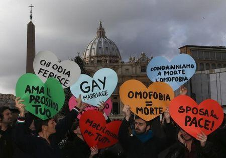 Members of a gay activist group hold signs in front of St. Peter's square in the Vatican