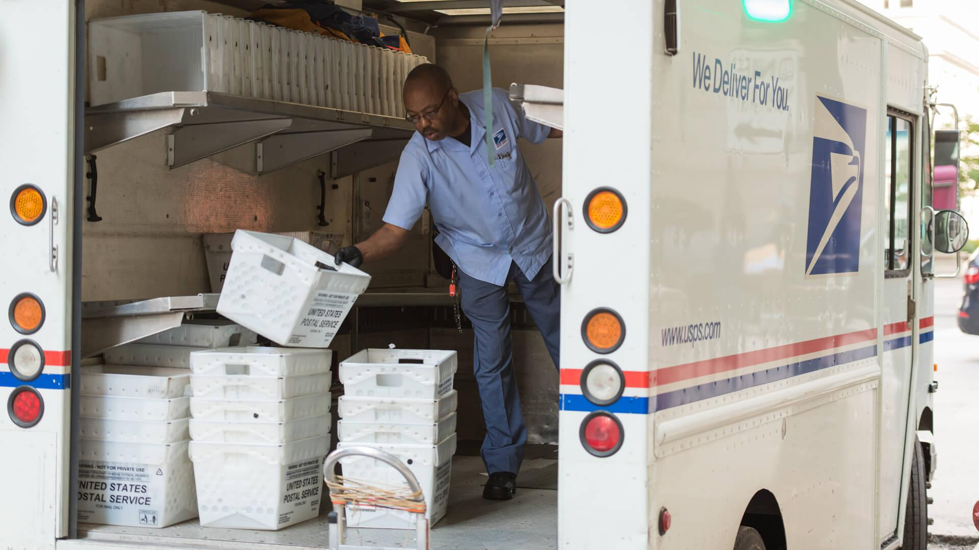 Chicago, USA - September 10, 2015: A USPS deliveryman sorting in the back of his truck on LaSalle street in the Loop late in the day.
