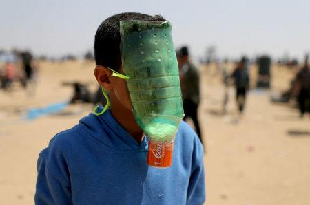 A Palestinian protects himself from inhaling tear gas at the Israel-Gaza border during a protest demanding the right to return to their homeland, in the southern Gaza Strip April 6, 2018. REUTERS/Ibraheem Abu Mustafa