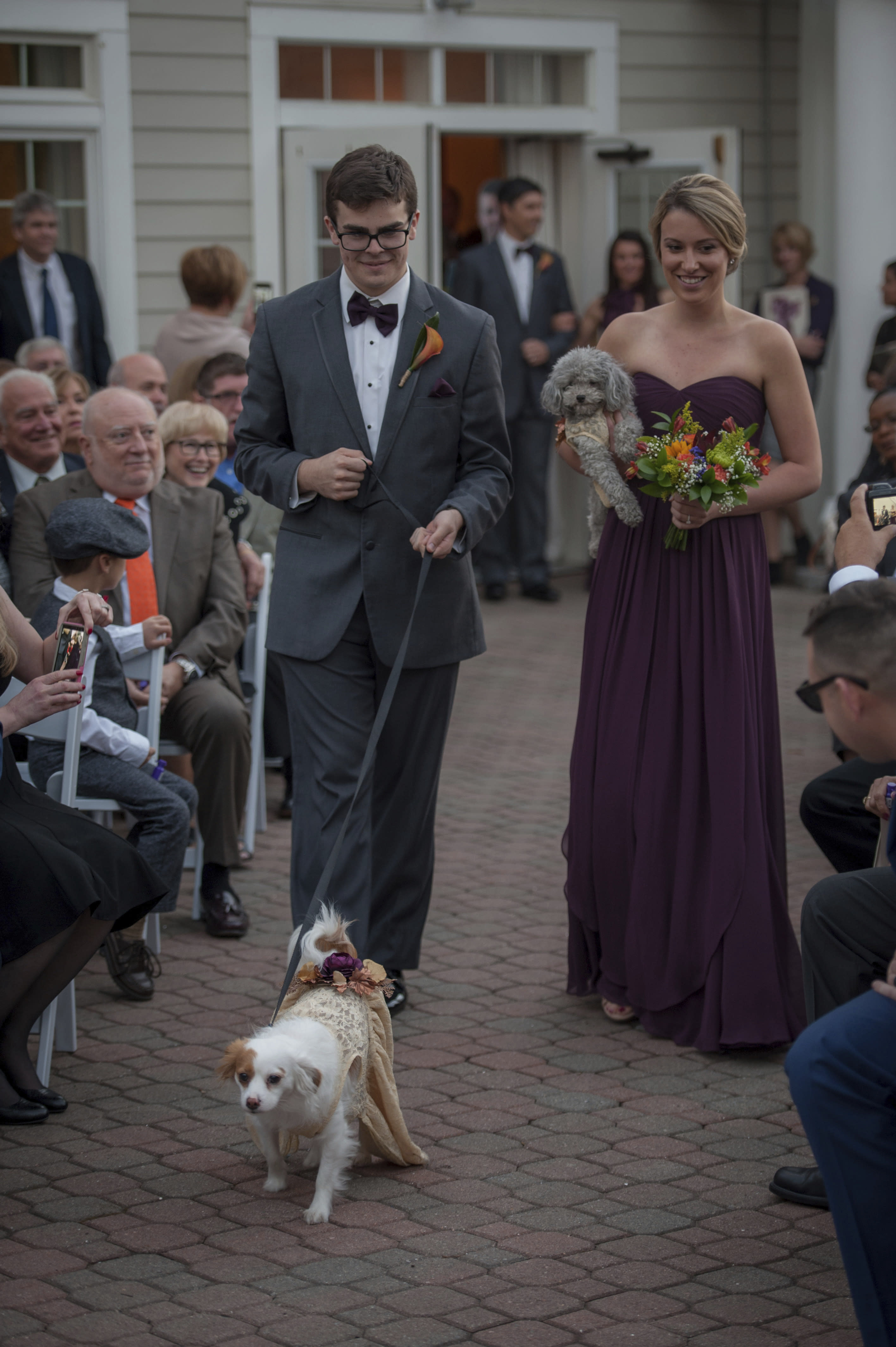 This Oct. 27, 2017 photo shows Ryan Curry and Laura Moylan walking Izzy, right, and Zoey down the aisle during the wedding of Kelly Curry and Patrick St. Onge in Haddam, Conn. The bride and groom's dogs took part in the ceremony. It's no longer unusual for brides and grooms to include pets in their wedding photos or even in the ceremony. But it can be tough to manage that along with everything else. (Jeffrey Herget/Studio 393 via AP)