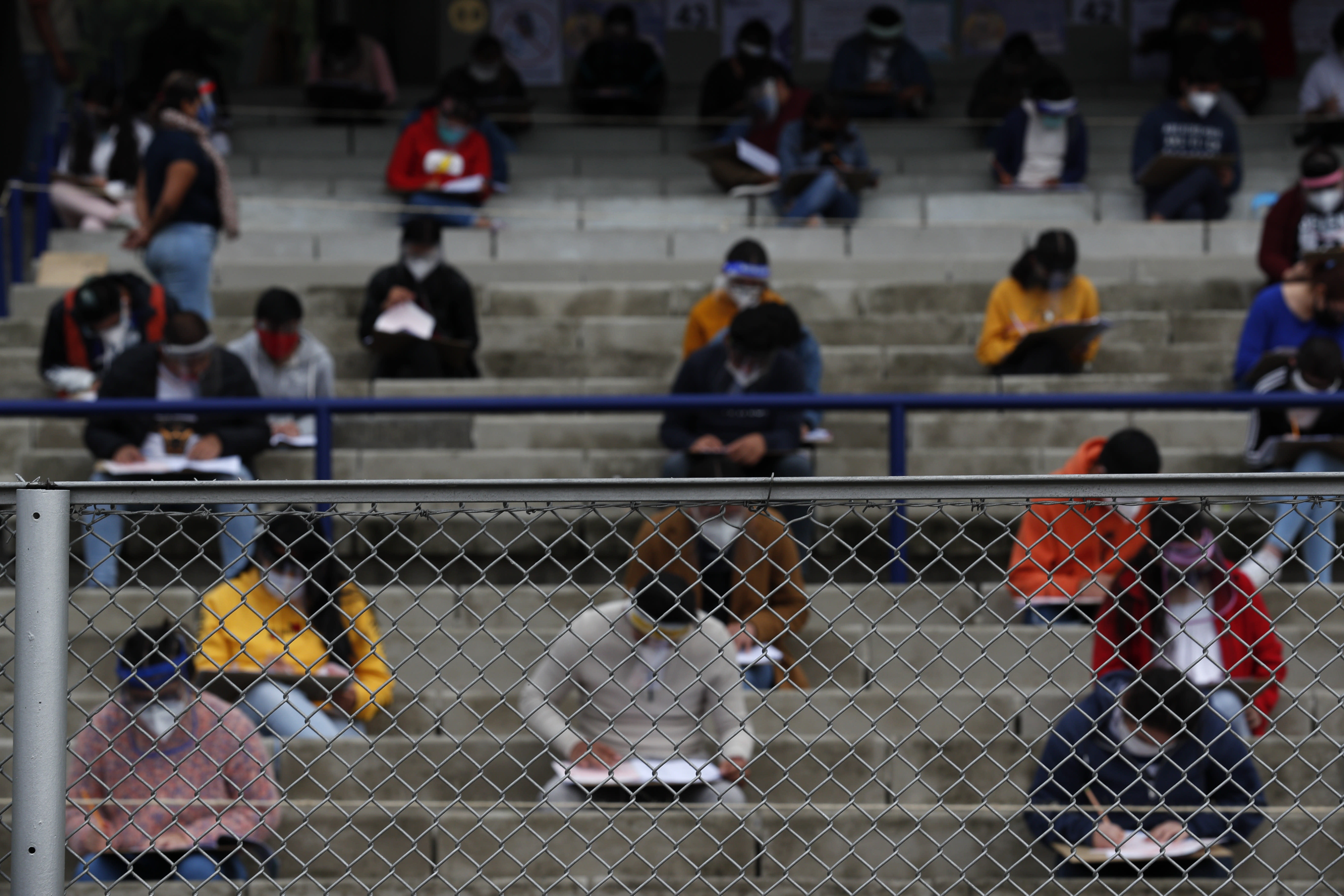 Prospective students are seen through a fence as they take the entrance exam for Mexico's National Autonomous University in the stands of University Olympic Stadium, amidst the ongoing coronavirus pandemic, in Mexico City, Wednesday, Aug. 19, 2020. More than 2,000 hopefuls registered to take the exam at the stadium, where it was being offered for the first time, and more than 80,000 aspirants were registered nationwide to take the exam. (AP Photo/Rebecca Blackwell)