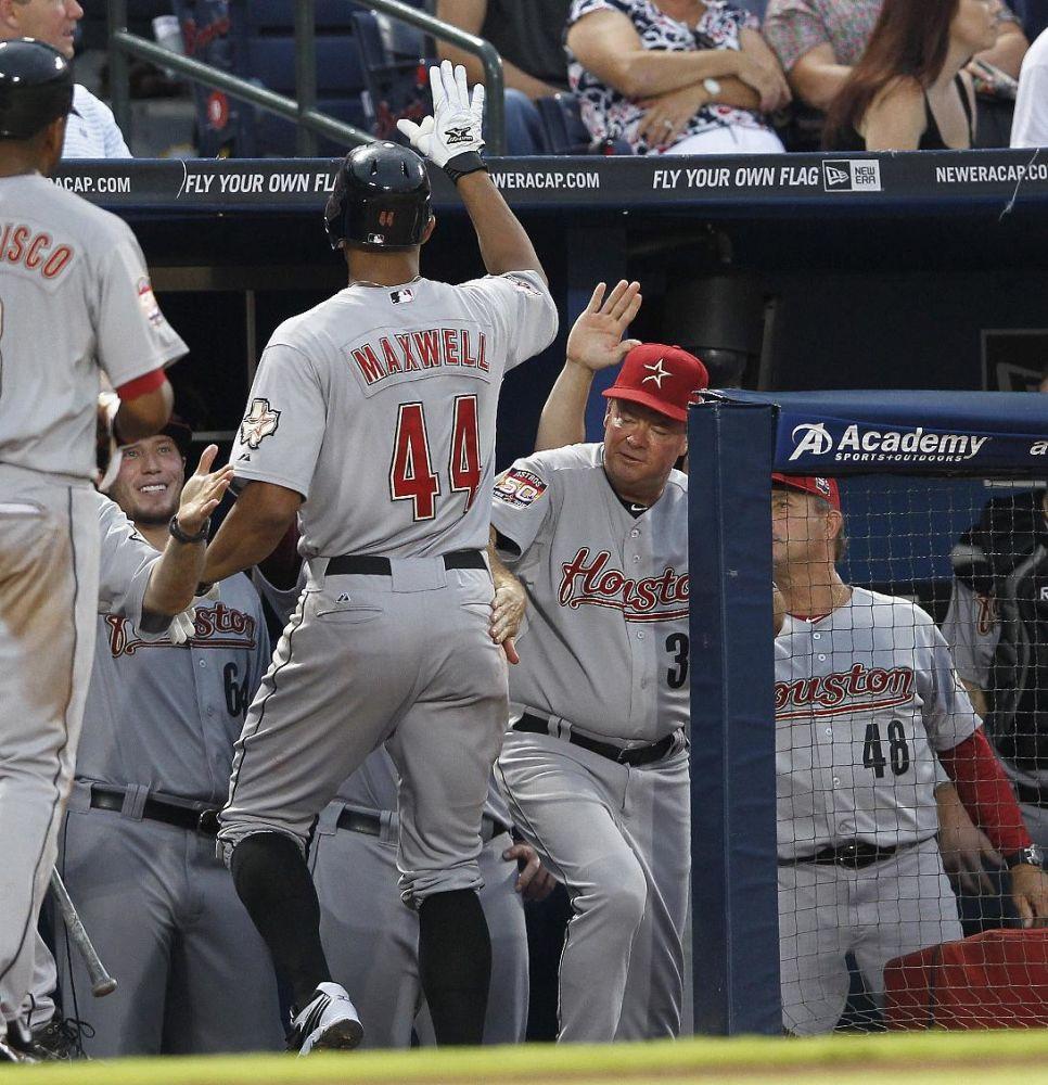 Justin Maxwell (44), de los Astros de Houston, es felicitado en el dugout después de batear un cuadrangular de dos carreras contra los Bravos de Atlanta, en la cuarta entrada del juego del sábado 4 de agosto de 2012, en  Atlanta. (Foto AP/John Bazemore)