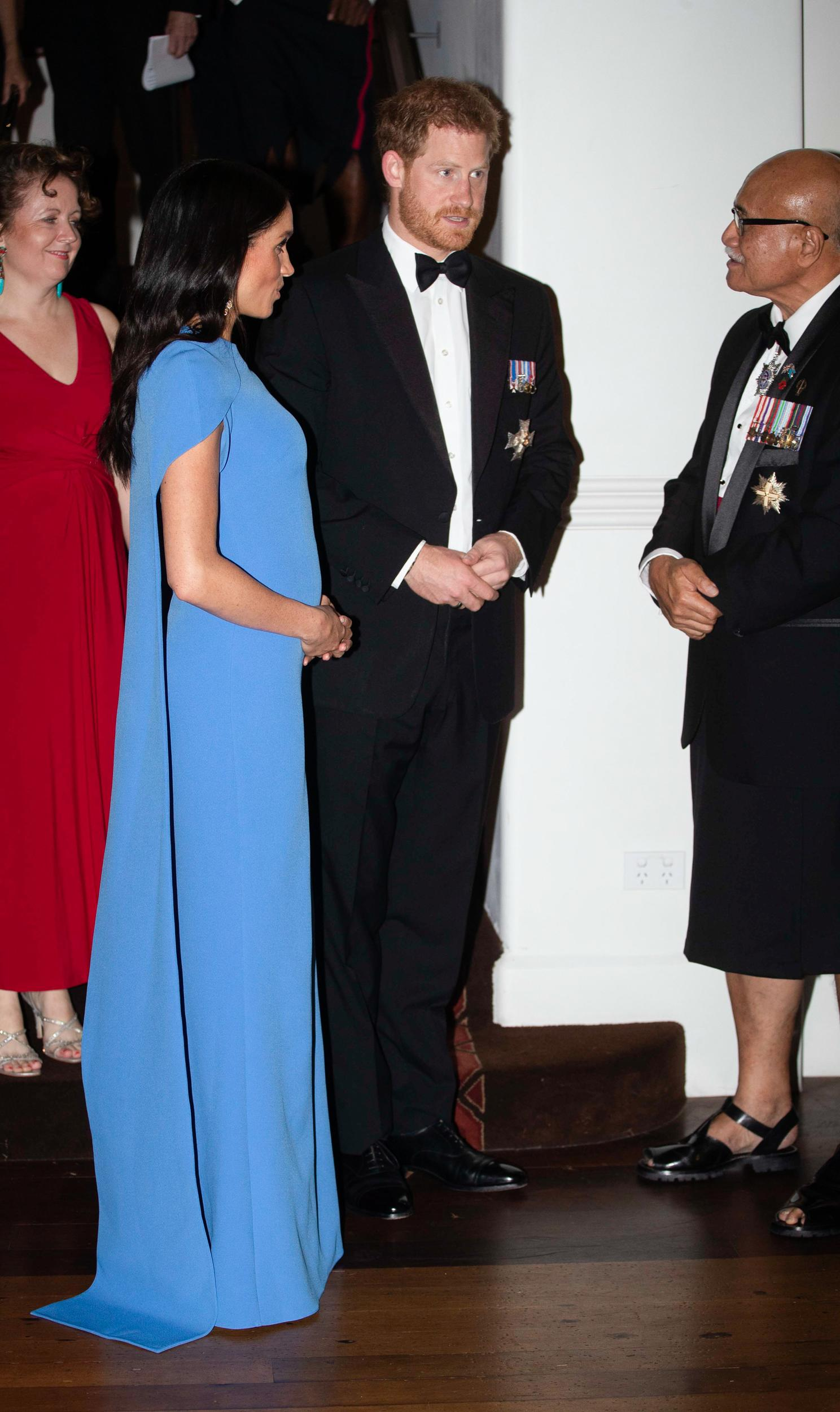 """Duchess Meghan stuns in Fiji blue<a href=""""https://www.net-a-porter.com/us/en/Shop/Designers/Safiyaa"""" target=""""_blank"""">Safiyaa</a>cape gown to attend a welcome ceremony hosted by Fiji's president."""