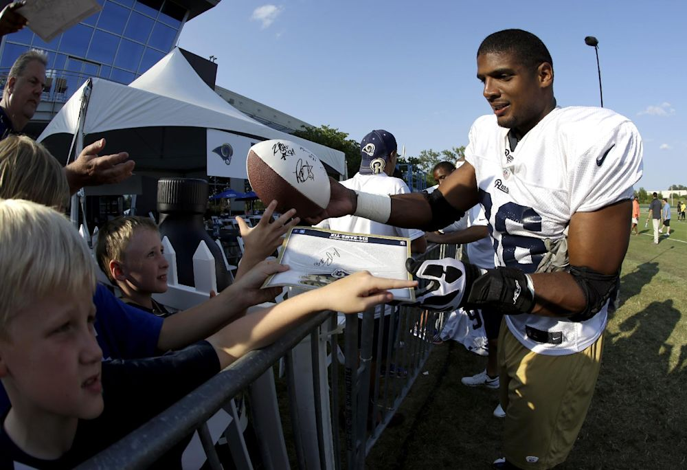 St. Louis Rams defensive end Michael Sam signs autographs for fans following practice at the NFL football team's training camp facility Tuesday, July 29, 2014, in St. Louis