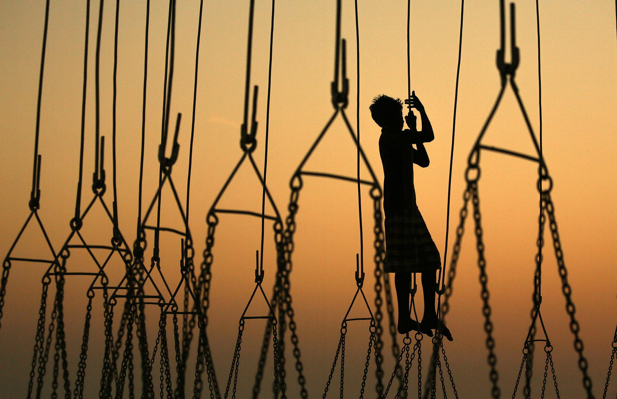 <p>An Indian boy plays with the carnival rides as he waits for customers in an amusement park during the annual Mahim Fair in Mumbai, India on Dec. 19, 2016. The ten-day fair features giant wheels, toy trains and gravity-defying stunts in the 'Maut Ka Kuan' or 'Well of Death' in honor of the Sufi saint Makhdoom Ali Mahimi. (Photo: Divyakant Solanki/EPA) </p>