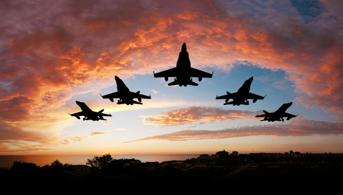 Five fighters flying at sunset