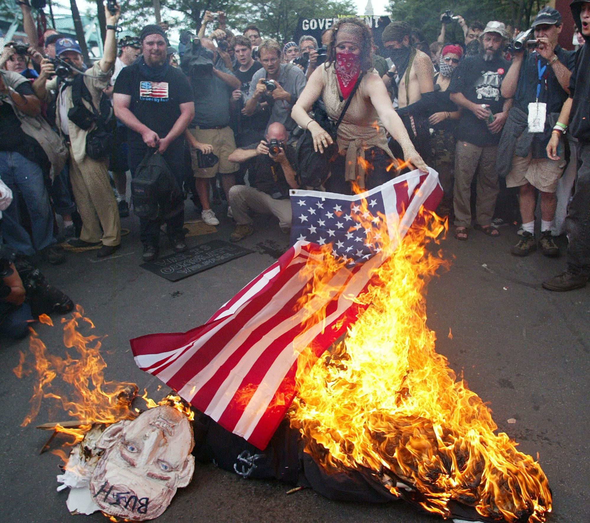 <p>Protesters burn an American flag and an effigy of President Bush and Sen. John Kerry on the last day of the Democratic National Convention in Boston, Thursday, July 29, 2004. (AP Photo/Rick Bowmer) </p>