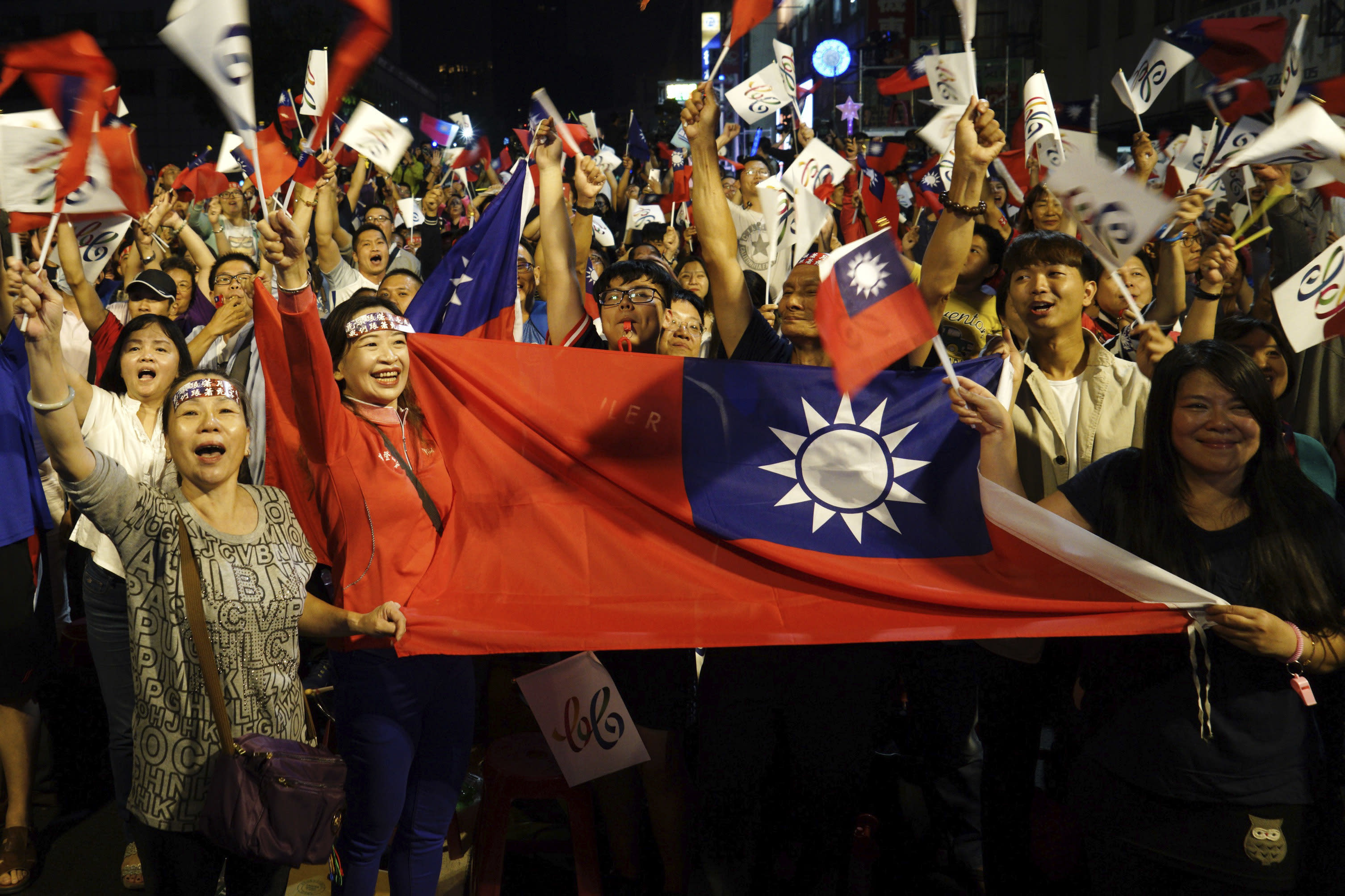 Supporters of the opposition Nationalist Party cheer in Kaohsiung, Taiwan, Saturday, Nov. 24, 2018. Taiwan's ruling party suffered a major defeat Saturday in local elections seen as a referendum on the administration of the island's independence-leaning president amid growing economic and political pressure from China. (AP Photo)