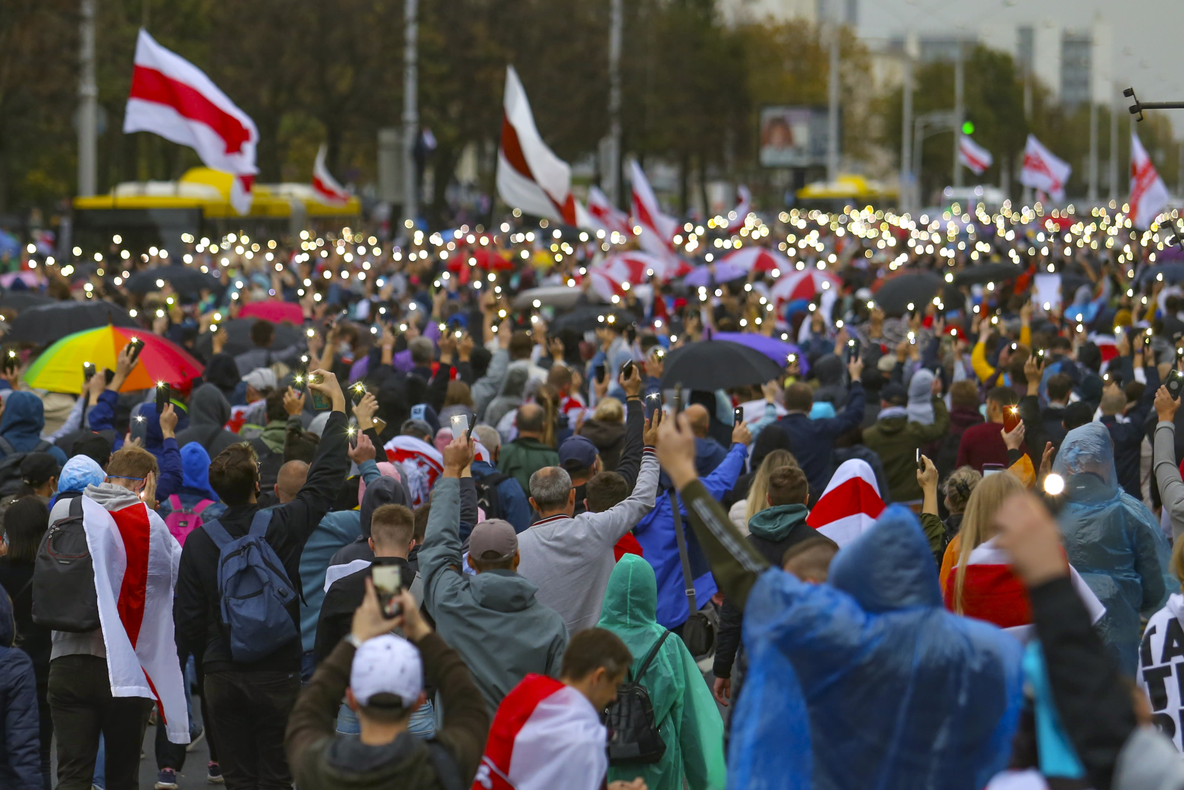Demonstrators light their cell phones during an opposition rally to protest the official presidential election results in Minsk, Belarus, Sunday, Sept. 27, 2020. Tens of thousands of demonstrators marched in the Belarusian capital calling for the authoritarian president's ouster, some wearing cardboard crowns to ridicule him, on Sunday as the protests that have rocked the country marked their 50th consecutive day. (AP Photo/TUT.by)