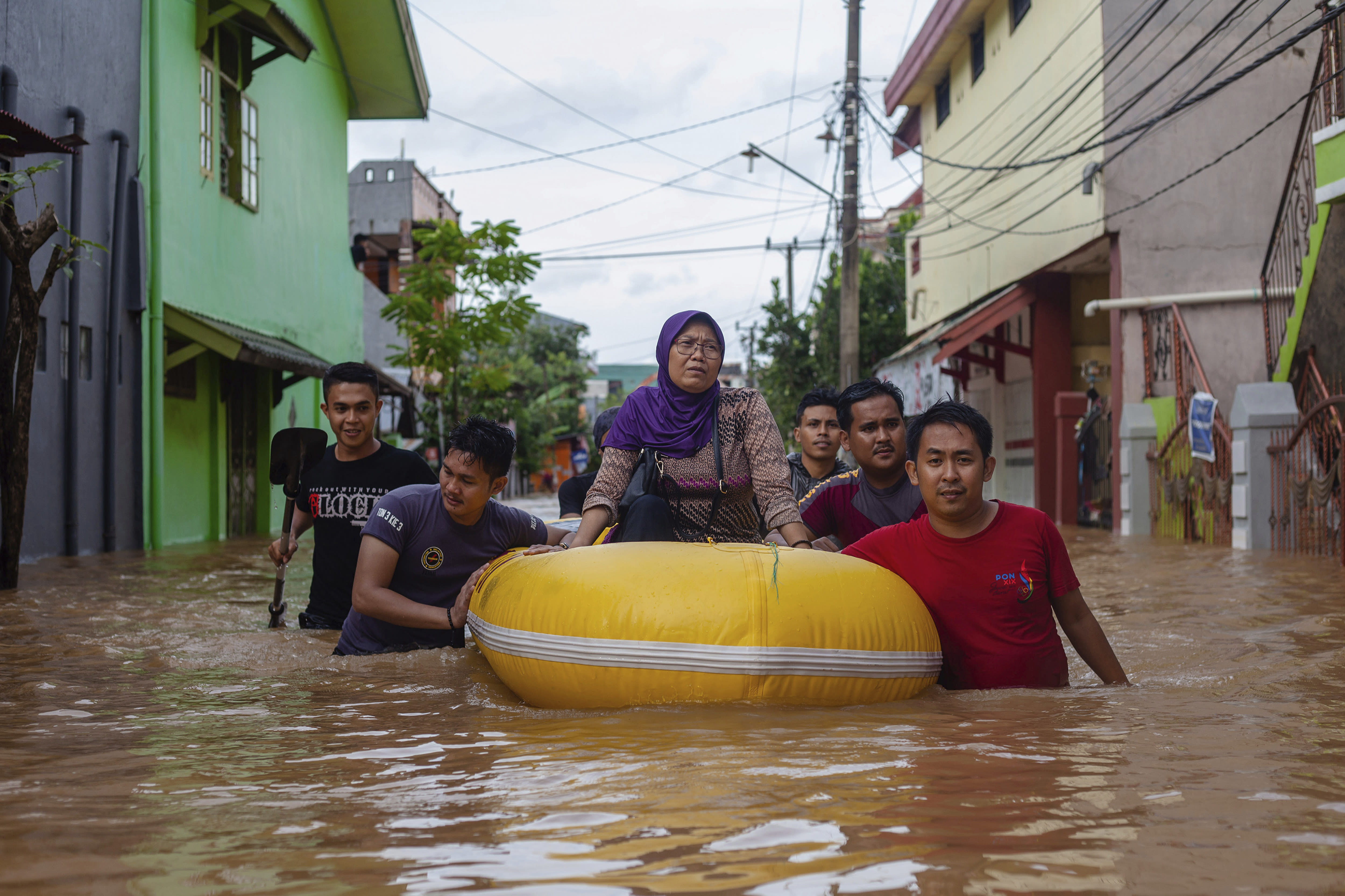 A woman sits on a rubber boat as she is evacuated from a flooded neighborhood in Makassar, South Sulawesi, Indonesia, Wednesday, Jan. 23, 2019. Torrential rains that overwhelmed a dam and caused landslides killed at least six people and displaced more than 2,000 in central Indonesia, officials said Wednesday. (AP Photo/Yusuf Wahil)