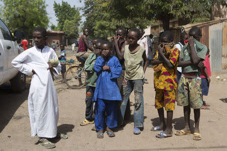 Children watch as health workers spray disinfectants at a mosque in Bamako